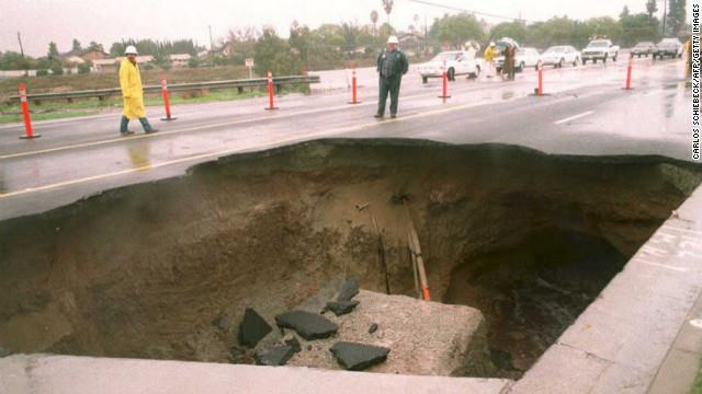 A 30-foot-deep sinkhole appeared in a busy street in a suburb east of downtown Los Angeles.