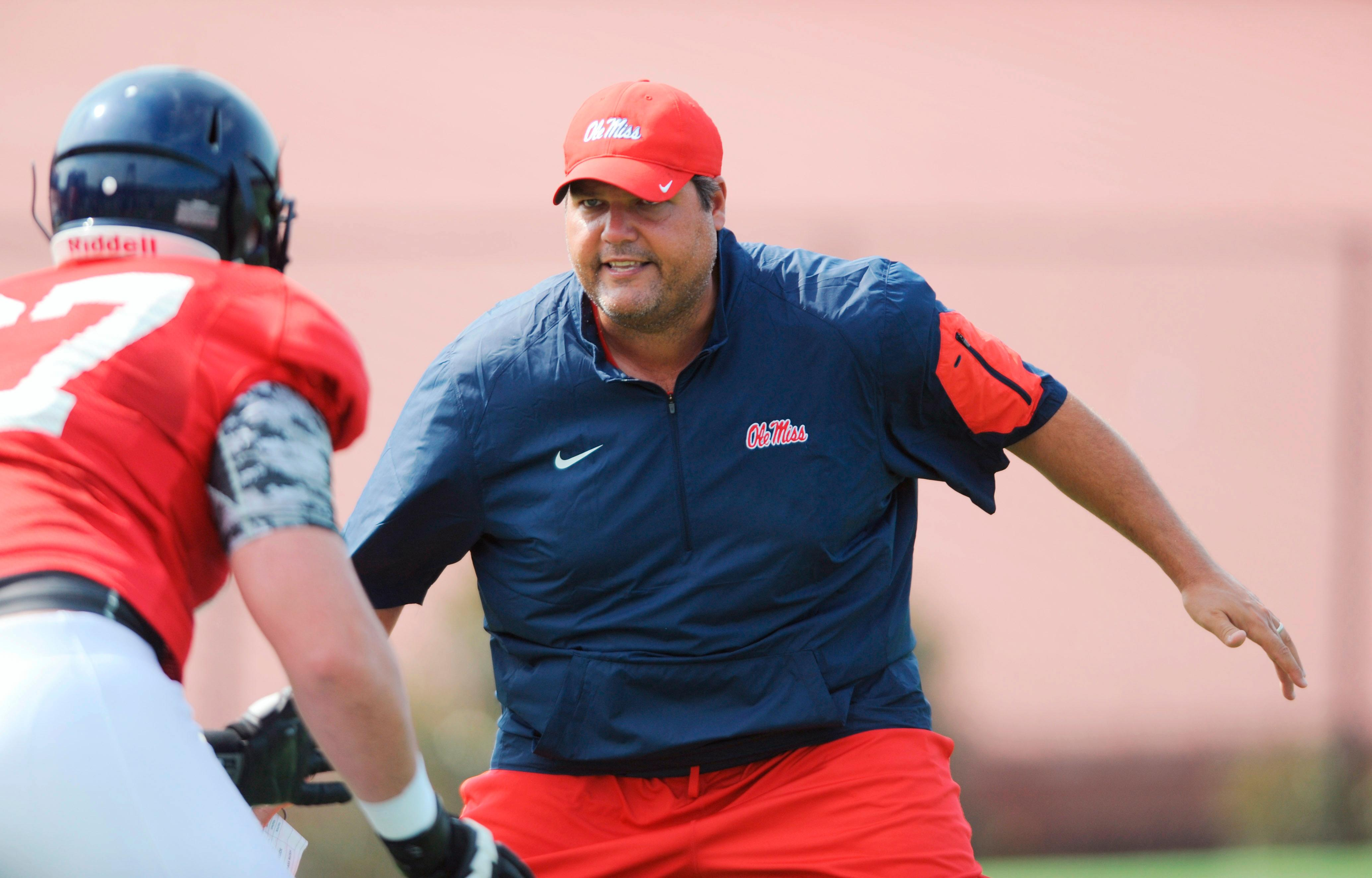 FILE - In this Aug. 10, 2015, file photo, Mississippi offensive line coach Matt Luke works on a drill with linemen during NCAA college football practice in Oxford, Miss. Mississippi coach Hugh Freeze has resigned after five seasons, bringing a stunning end to a once-promising tenure. The school confirmed Freeze's resignation in a release Thursday night, July 20, 2017. Luke has been named the interim coach. (Bruce Newman/The Oxford Eagle via AP, File)