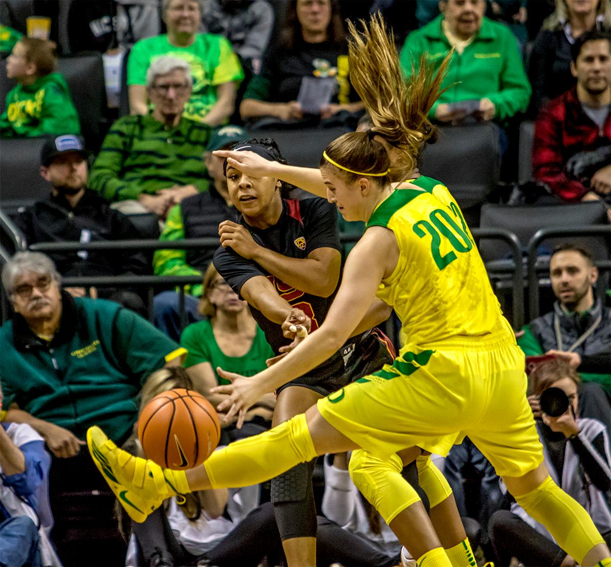 the Trojan's Minyon Moore (#3) passes the ball by the Duck's Sabrina Ionescu (#20). The Oregon Ducks defeated the USC Trojans 80-74 on Friday at Matthew Knight Arena in a  game that went into double overtime. Lexi Bando sealed the Ducks victory by scoring a three-pointer in the closing of the game. Ruthy Hebard set a new NCAA record of 30 consecutive field goals, the old record being 28. Ruthy Hebard got a double-double with 27 points and 10 rebounds, Mallory McGwire also had 10 rebounds. The ducks had four players in double digits. The Ducks are now 24-4, 13-2 in the Pac-12, and are tied for first with Stanford. Photo by August Frank, Oregon News Lab