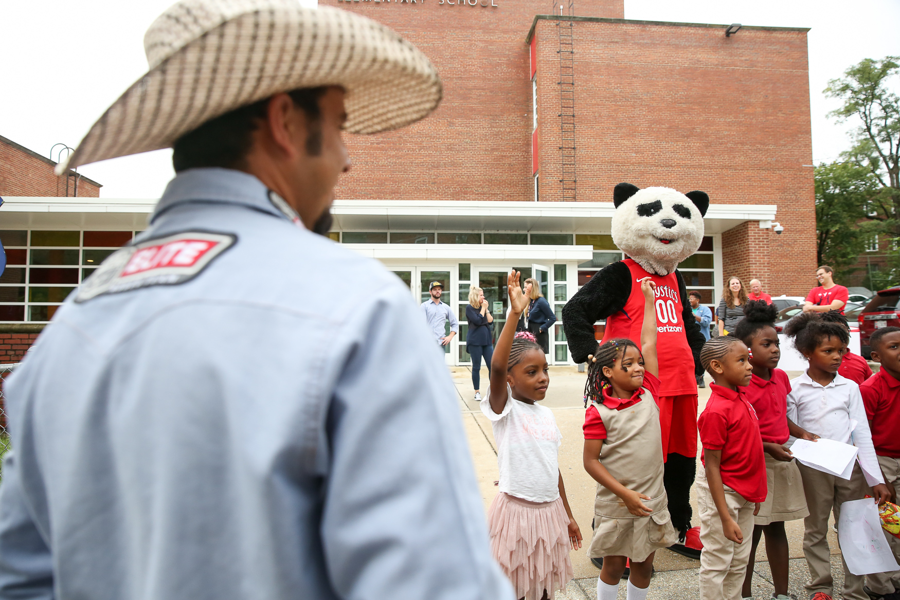 Kids at{ }Hendley Elementary School had some very special guests today.{ }Bull rider{ }Matt Triplett, Washington Mystics mascot Pax the Panda and several cowboys stopped by Hendley Elementary to give them some lessons about bull riding and deliver a gift - $2,000{ }{ }to the MSE Foundation so that students can have access to computers. The team stopped in Anacoastia{ }ahead of the{ }PBR (Professional Bull Riders) Elite tour stop in Fairfax, VA, this weekend. The main attraction for the kids wasn't the money or the cowboys though - they couldn't keep their eyes off of Million Dollar Baby, a bull set to compete in the PBR Elite Tour. (Amanda Andrade-Rhoades/DC Refined)