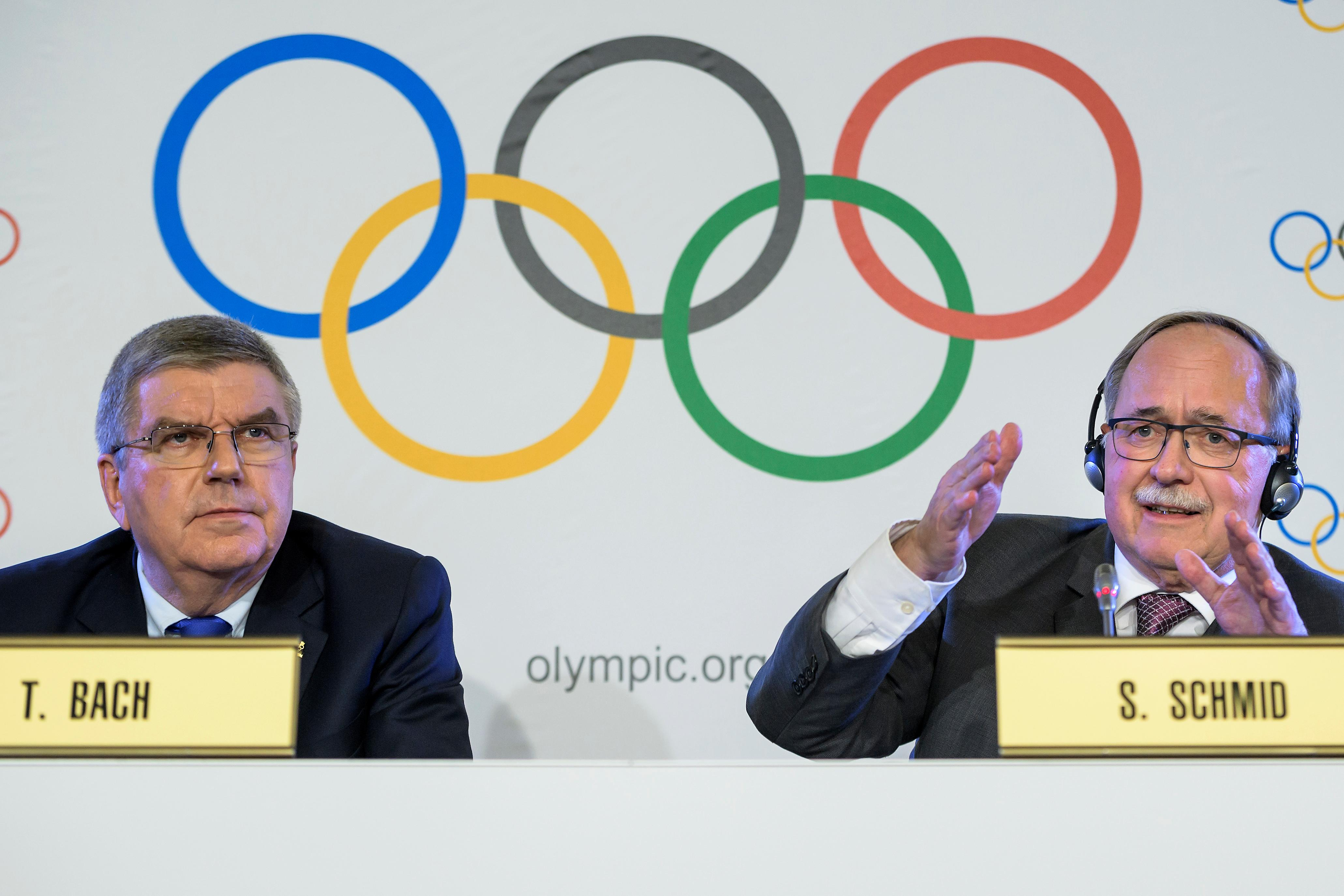 International Olympic Committee, IOC, President Thomas Bach from Germany, left, and Samuel Schmid, President of the IOC Inquiry Commission and former President of Switzerland, right, react during a press conference after an Executive Board meeting, in Lausanne, Switzerland, Tuesday, Dec. 5, 2017. Russian athletes will be allowed to compete at the upcoming Pyeongchang Olympics as neutrals despite orchestrated doping at the 2014 Sochi Games, the International Olympic Committee said Tuesday. (Jean-Christophe Bott/Keystone via AP)