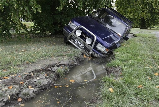 A car lies in a crevice caused by Tuesday's earthquake. / AP photo