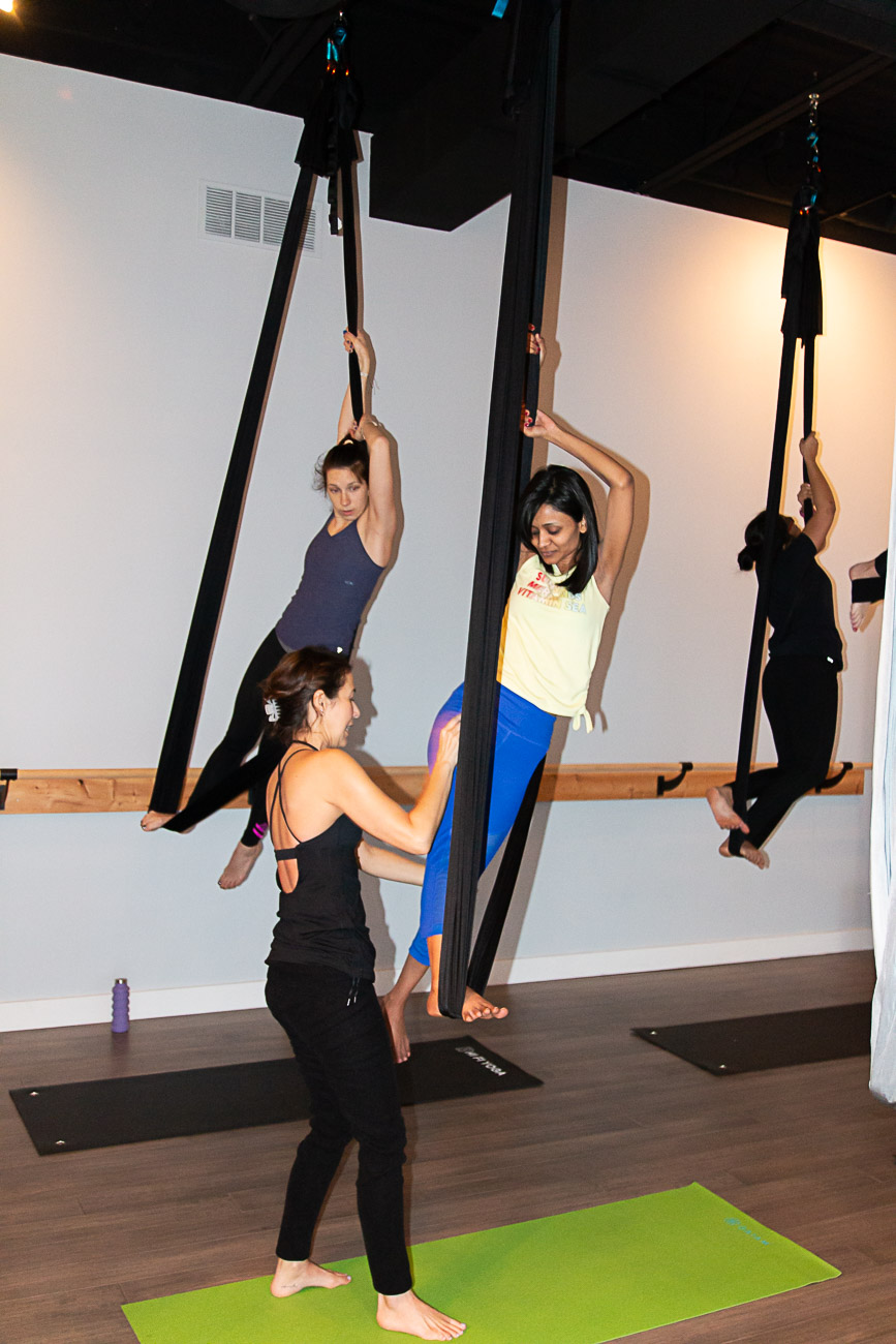 "Aerial yoga is practiced with the aid of nine ""silks"" suspended from the ceiling. These silks support your body in various poses while you are suspended from the ground. Allen and Moorman wanted to include aerial in their studio because they recognize you can only go so far on your mat physically. The style of yoga allows you to go deeper into poses and stretches, making it ideal for people with tight backs, shoulders, hamstrings, or hips. It can also be a game-changer for people who struggle with flexibility or injuries. / Image: Elizabeth A. Lowry // Published: 3.5.20"