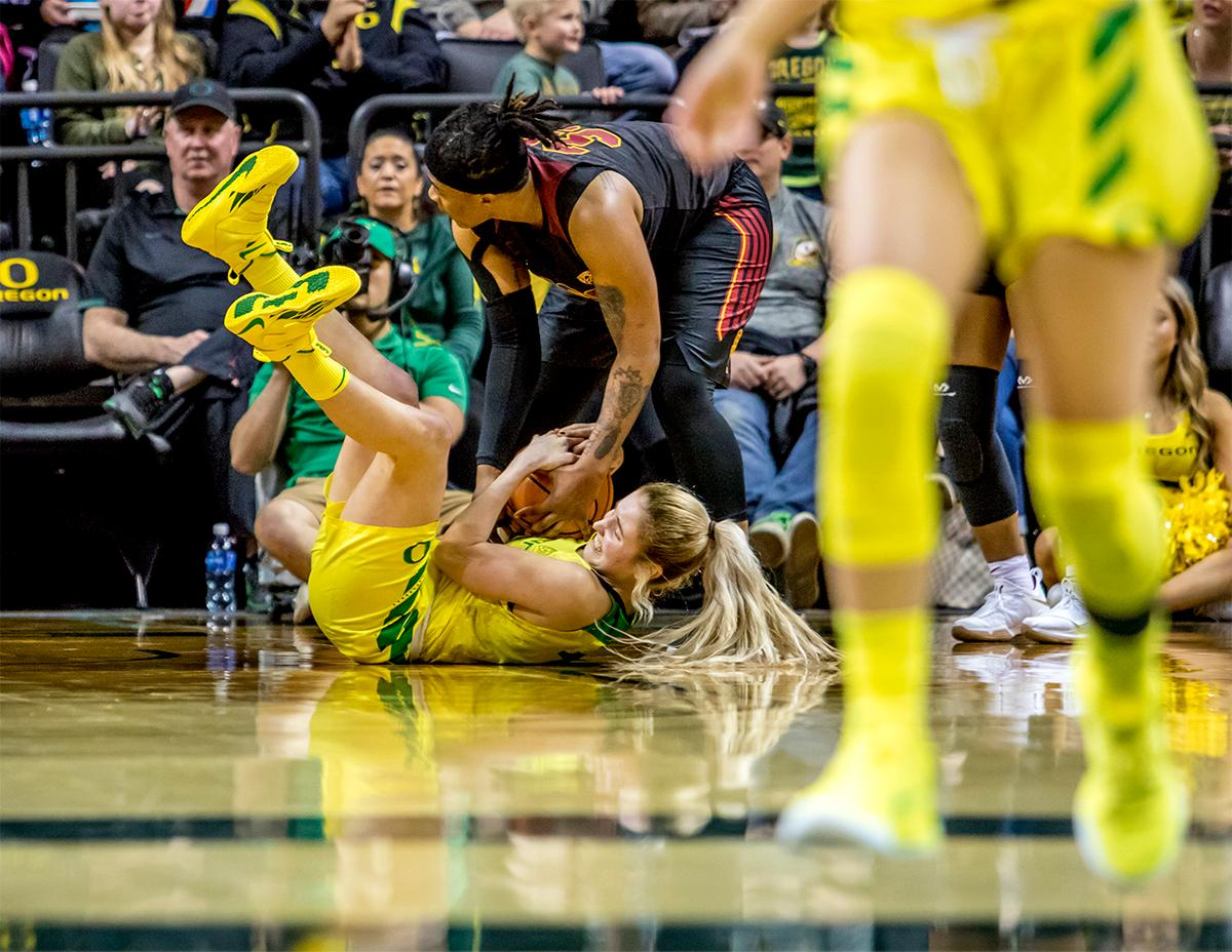 The Duck's Anneli Maley (#15) grips the ball tightly as a Trojan's player tries to steal it. The Oregon Ducks defeated the USC Trojans 80-74 on Friday at Matthew Knight Arena in a  game that went into double overtime. Lexi Bando sealed the Ducks victory by scoring a three-pointer in the closing of the game. Ruthy Hebard set a new NCAA record of 30 consecutive field goals, the old record being 28. Ruthy Hebard got a double-double with 27 points and 10 rebounds, Mallory McGwire also had 10 rebounds. The ducks had four players in double digits. The Ducks are now 24-4, 13-2 in the Pac-12, and are tied for first with Stanford. Photo by August Frank, Oregon News Lab