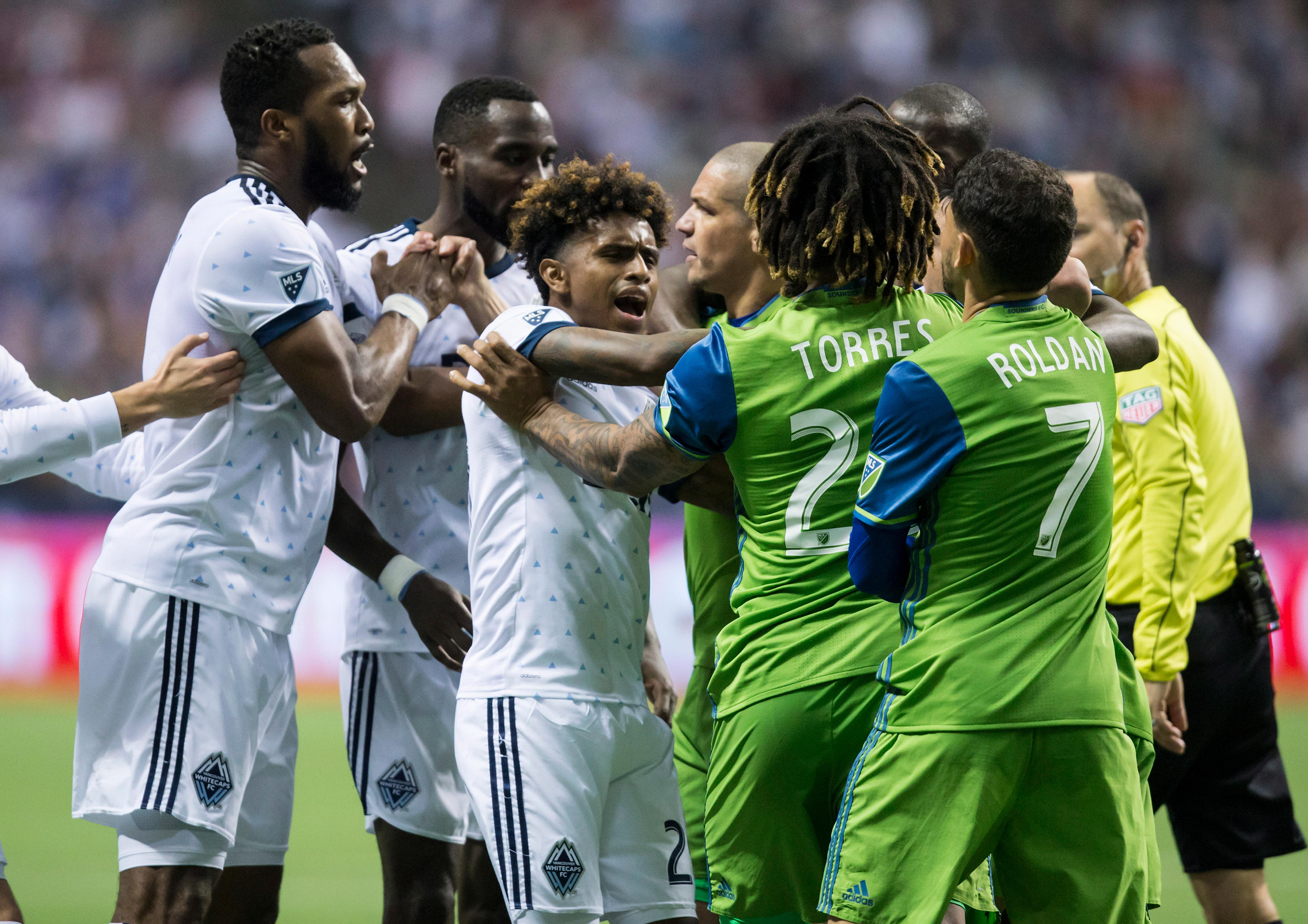 Vancouver Whitecaps' Kendall Waston, left, and Yordy Reyna, center left, get into a scuffle with Seattle Sounders' Osvaldo Alonso, center right, and Roman Torres during the second half of an MLS playoff soccer match in Vancouver, British Columbia, Sunday, Oct. 29, 2017. (Darryl Dyck/The Canadian Press via AP)