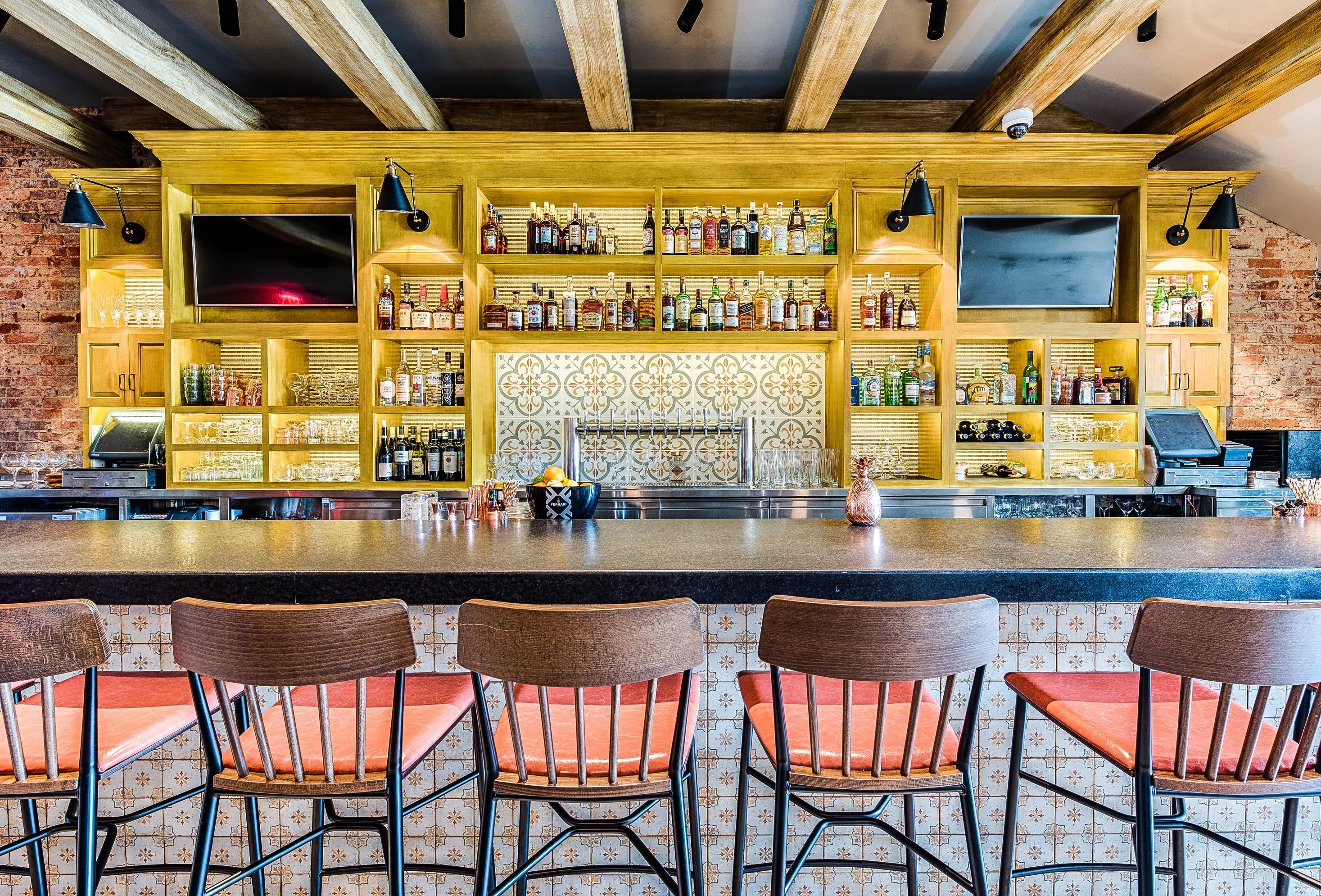 Cozy up to the bar, where you can observe prosciutto being gracefully sliced or simply watch television. (Image: Rey Lopez)