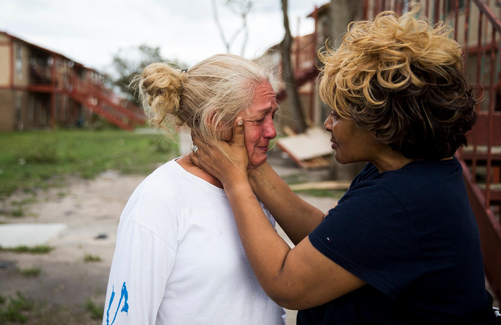 "Genice Gipson comforts her lifelong friend, Loretta Capistran, outside of Capistran's apartment complex in Refugio, Texas, on Monday, Aug. 28, 2017. ""We got to be strong, baby,"" Gipson told Capistran. (Nick Wagner/Austin American-Statesman via AP)"