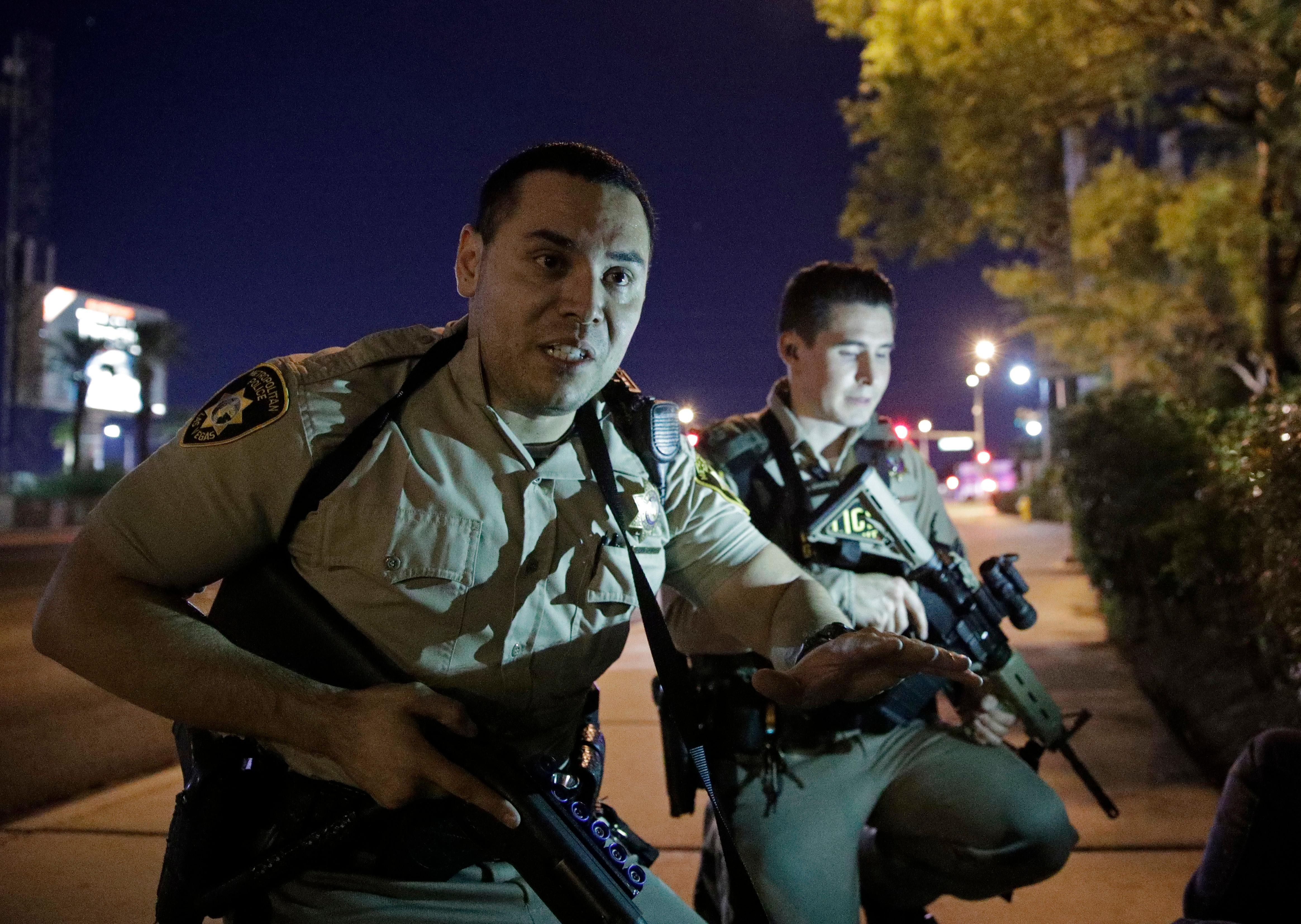 Police officers advise people to take cover near the scene of a shooting near the Mandalay Bay resort and casino on the Las Vegas Strip, Sunday, Oct. 1, 2017, in Las Vegas. (AP Photo/John Locher)