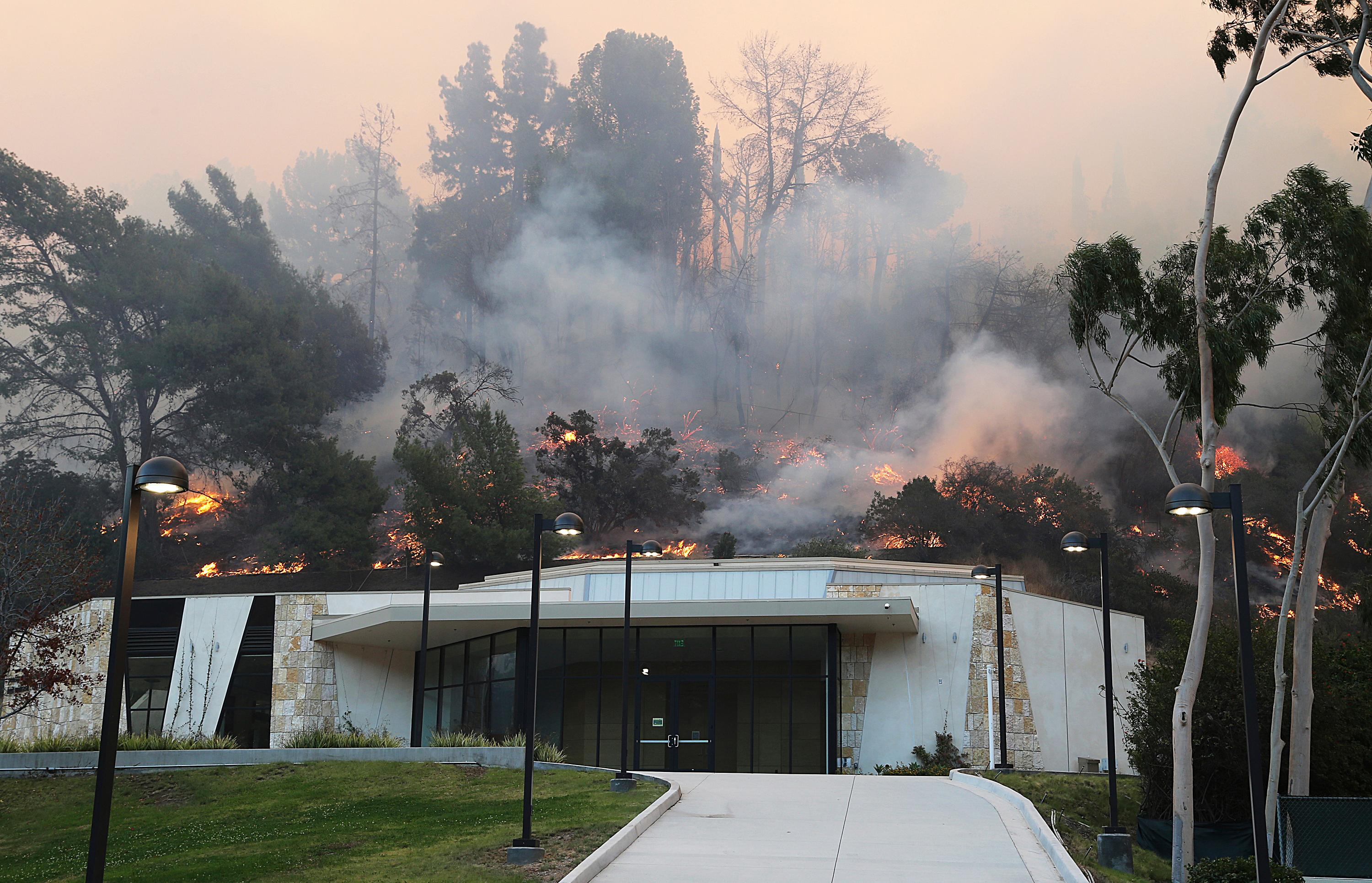 Flames from a wildfire work their way down a slope behind Leo Baeck Temple in Sepulveda Pass in the Bel Air district of Los Angeles Wednesday, Dec. 6, 2017. (AP Photo/Reed Saxon)