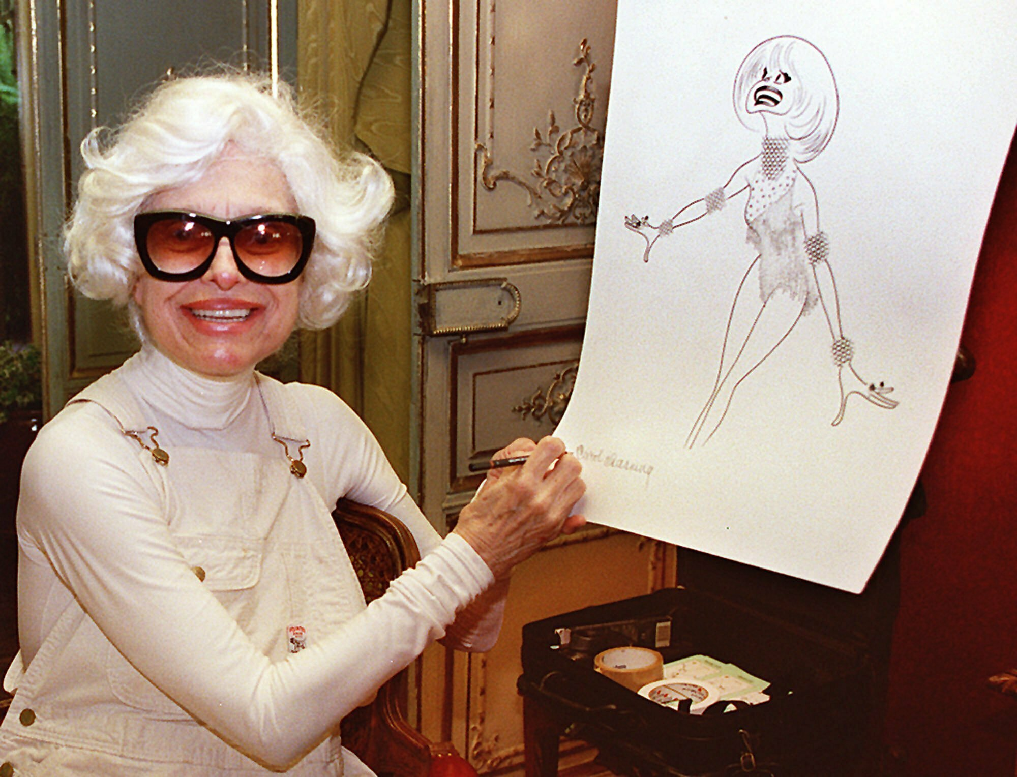 FILE - In this Nov. 1, 1997 file photo, actress Carol Channing hand-signs a lithograph of herself by caricaturist Al Hirschfeld at her home in Beverly Hills, Calif.  Channing, whose career spanned decades on Broadway and on television has died at age 97. Publicist B. Harlan Boll says Channing died of natural causes early Tuesday, Jan. 15, 2019 in Rancho Mirage, Calif. (AP Photo/Damian Dovarganes, File)