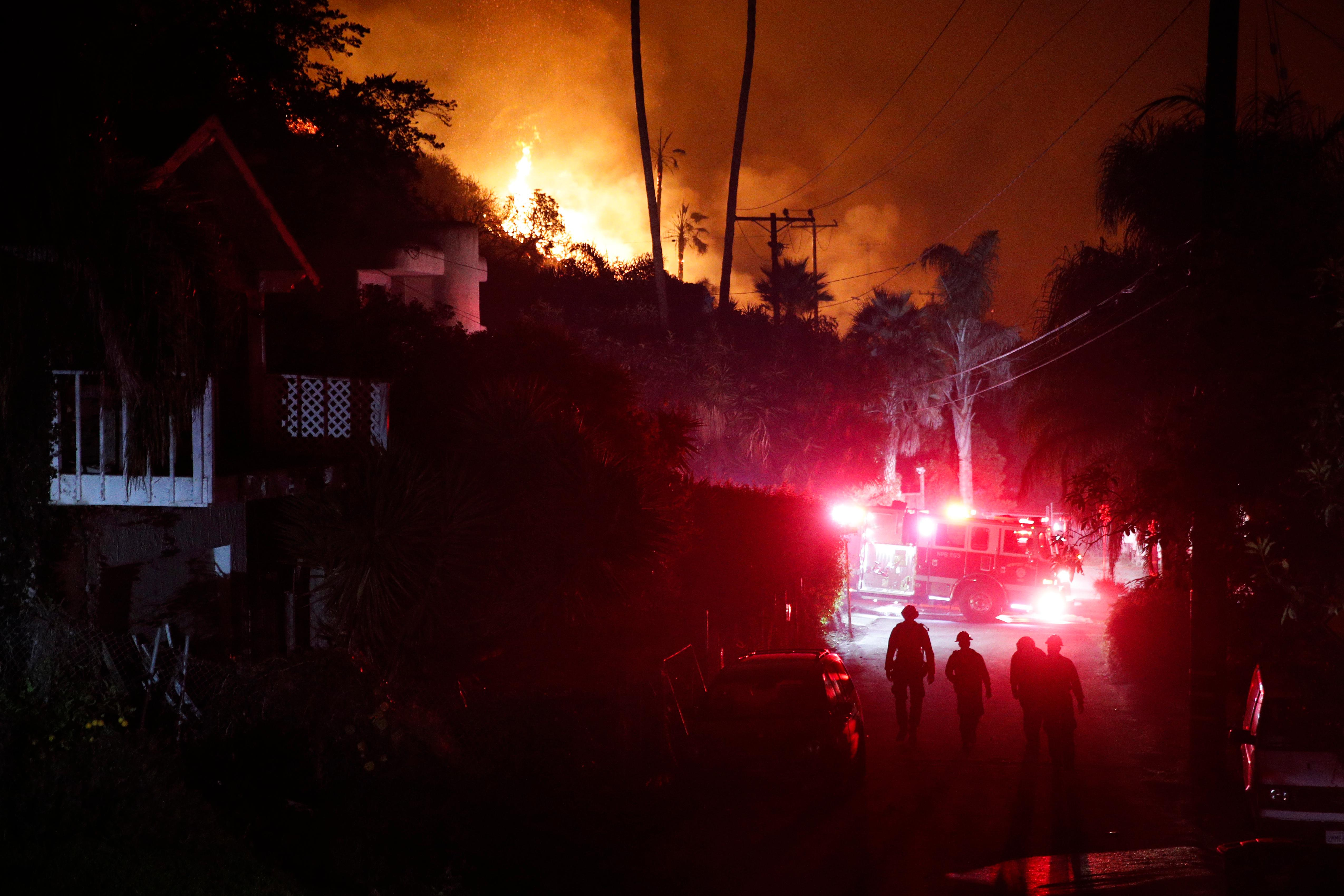 Firefighters walk along an alley as a wildfire burns along a hillside toward homes in La Conchita, Calif., Thursday, Dec. 7, 2017. The wind-swept blazes have forced tens of thousands of evacuations and destroyed dozens of homes. (AP Photo/Jae C. Hong)