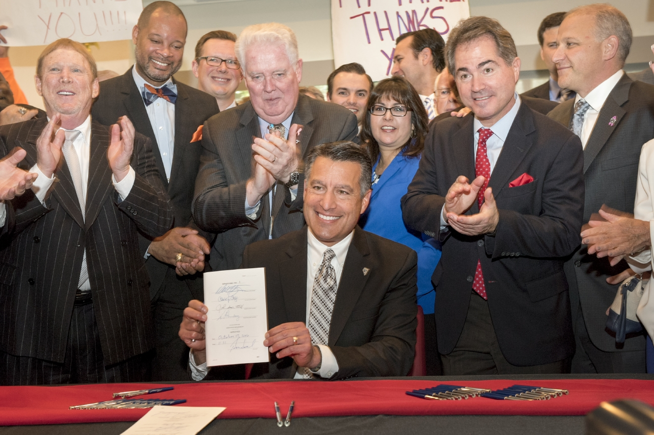 Nevada Gov. Brian Sandoval, center, holds Senate Bill 1, signed into law in a ceremony in UNLV's Tam Alumni Hall on Monday, Oct. 17, 2016. Senate Bill 1 authorizes the funds for the Las Vegas Convention Center District expansion as well as the construction of a 65,000 seat NFL footbal stadium. Oakland Raiders owner Mark Davis, left, and UNLV President Len Jessup, second from right, joined the ceremony along with Nevada legislators, gaming executives, labor union leaders and other Oakland Raiders officials. (Mark Damon/Las Vegas News Bureau)