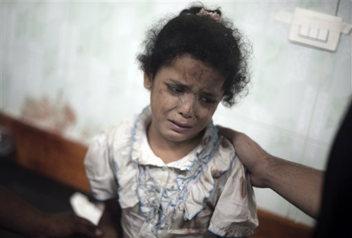 A Palestinian girl cries while receiving treatment for her injuries caused by an Israeli strike at a U.N. school in Jebaliya refugee camp.