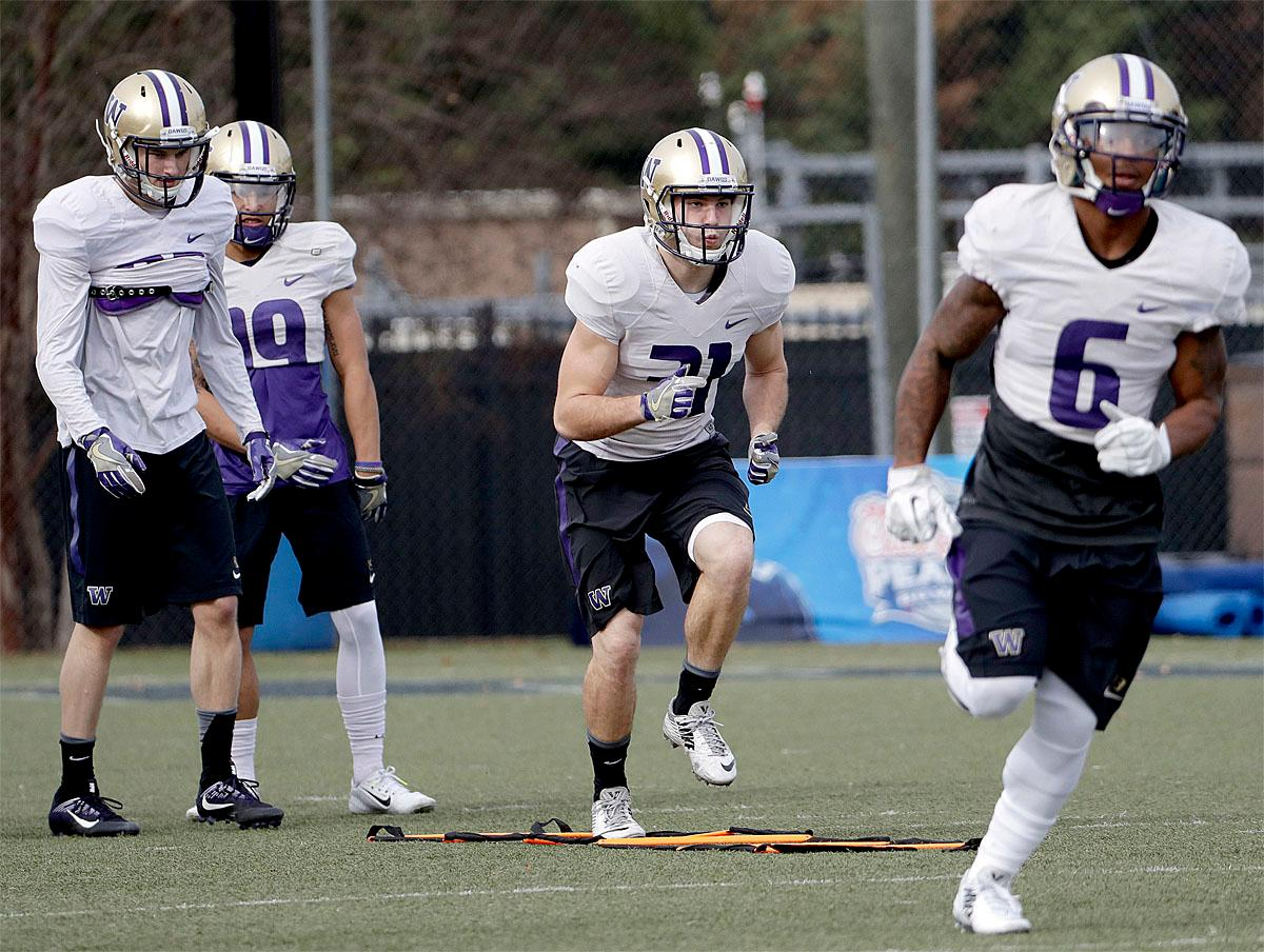 Washington's Drew Before, center, runs a drill during a Peach Bowl NCAA college football practice in Atlanta, Wednesday, Dec. 28, 2016. Alabama and Washington will face off in the Peach Bowl football game Saturday. (AP Photo/David Goldman)