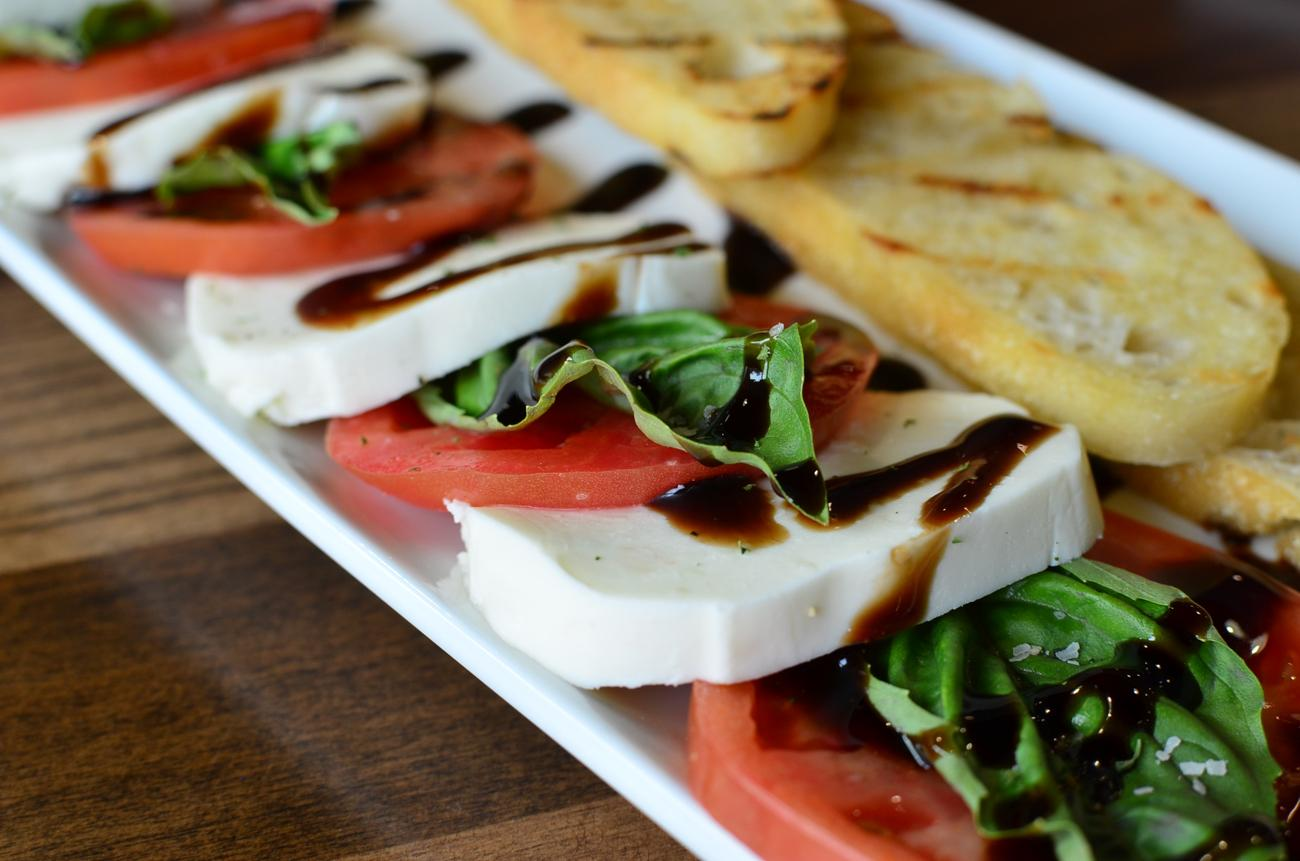 Caprese Bruschetta: fresh mozzarella, tomato, and basil layered together with rustic grilled bread, drizzled with orange balsamic vinegar reduction / Image: Leah Zipperstein, Cincinnati Refined // Published: 11.1.17