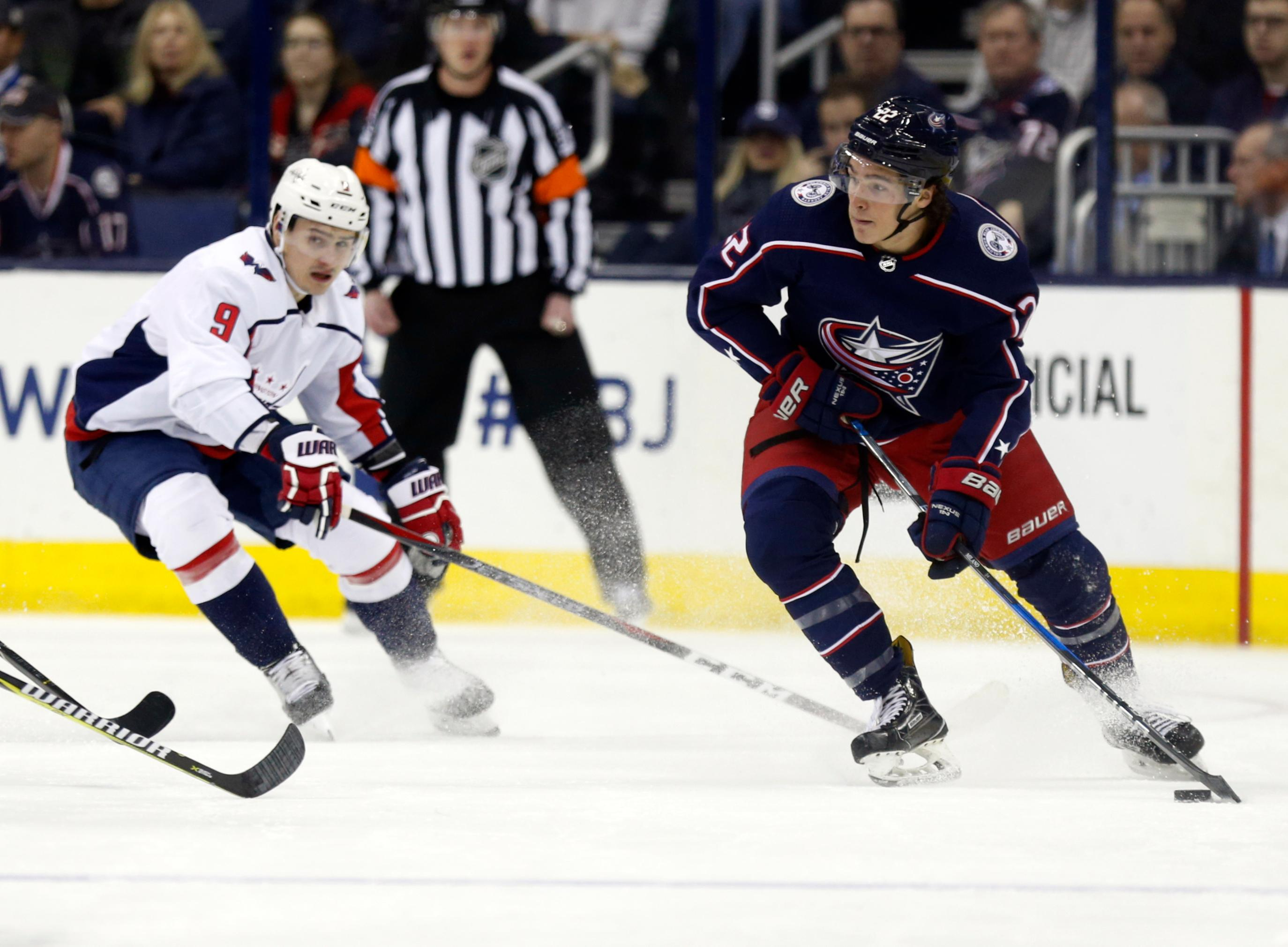 Columbus Blue Jackets forward Sonny Milano, right, controls the puck against Washington Capitals defenseman Dmitry Orlov, of Russia, during the first period of an NHL hockey game in Columbus, Ohio, Monday, Feb. 26, 2018. (AP Photo/Paul Vernon)