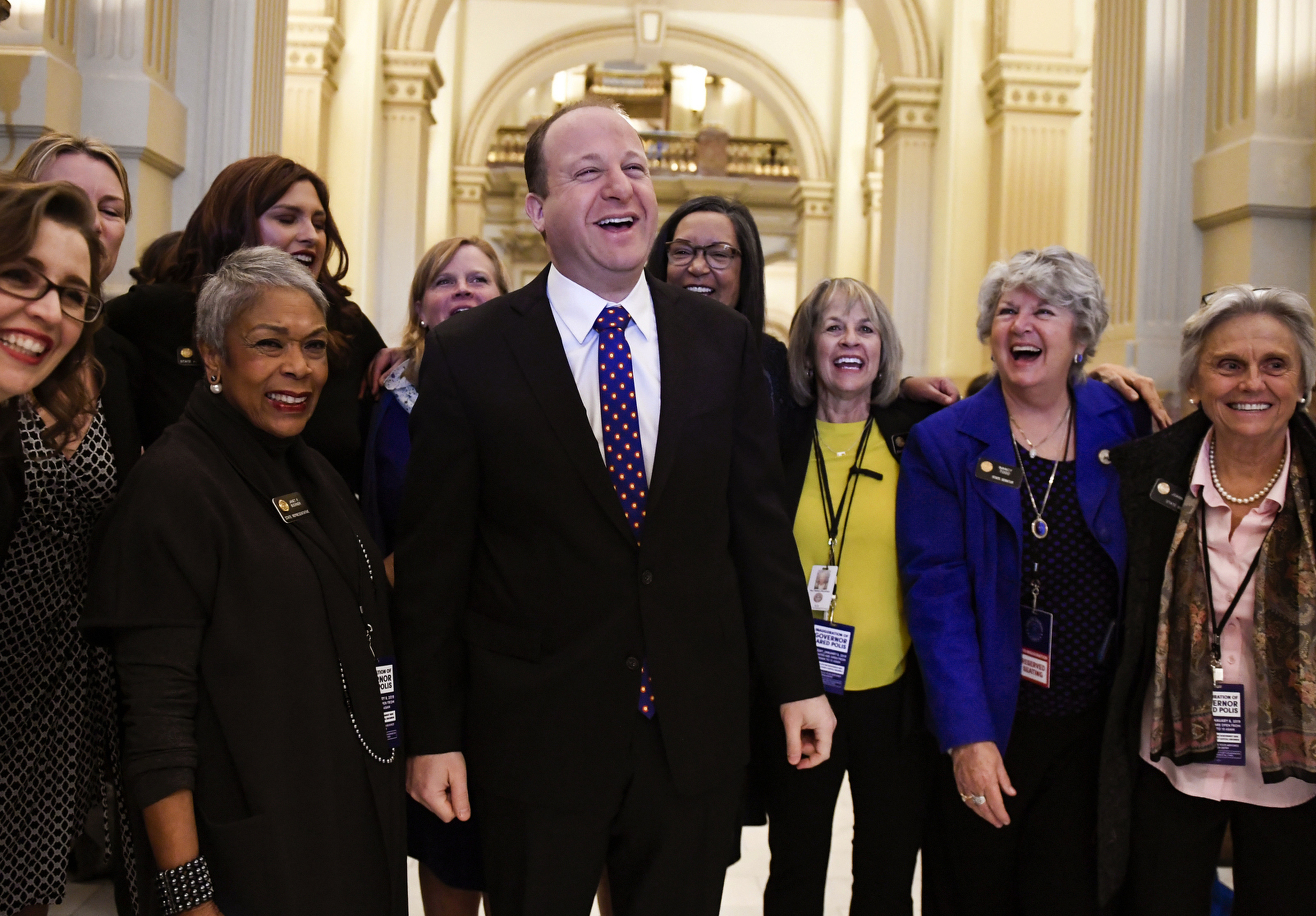 FILE - In this Tuesday, Jan. 8, 2019, file photo, Colorado Governor elect Jared Polis, center, jokes with members of the state house and senate before his inauguration at the Colorado State Capitol in Denver. Health care proposals are among the first actions for some new Democratic governors and Democratically controlled legislatures. Expanding access to care was a rallying point for the party in the 2018 elections.   (AAron Ontiveroz/The Denver Post via AP, File)