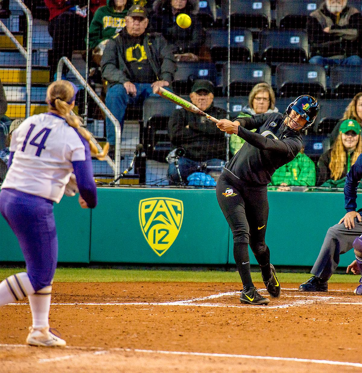 The Duck's Lauren Lindvall (#8) hits the ball high. In Game Two of a three-game series, the University of Oregon Ducks softball team defeated the University of Washington Huskies 4-1 Friday night in Jane Sanders Stadium. Danica Mercado (#2), Alexis Mack (#10) and Mia Camuso (#7) all scored in the win, Mack twice. The Ducks play the Huskies for the tie breaker on Saturday with the first pitch at noon. Photo by August Frank, Oregon News Lab