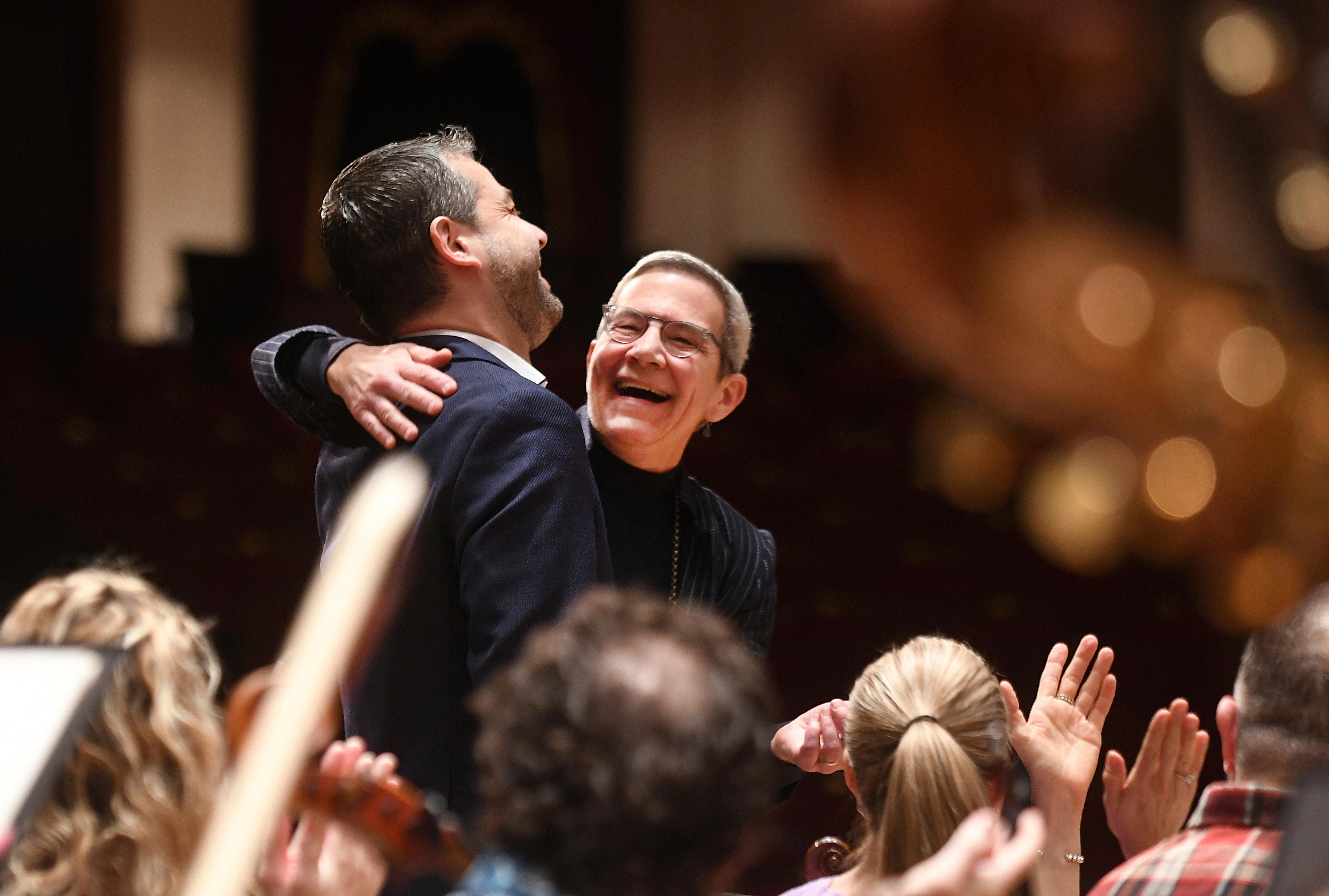 Italian conductor Jader Bignamini, center left, was named The Detroit Symphony Orchestra's new music director, and is hugged by DSO president and CEO Anne Parsons during a ceremony held at the Max M. Fisher Music Center in Detroit, on Wednesday, Jan. 22, 2020. (Max Ortiz/Detroit News via AP)