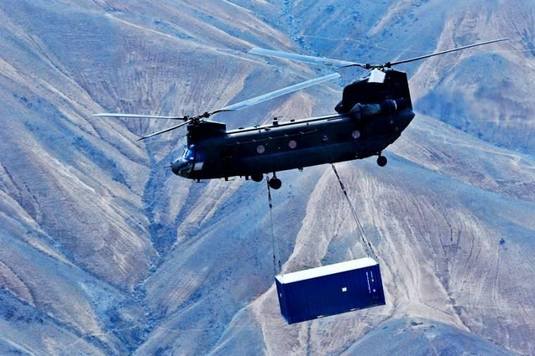 A U.S. Army CH-47 Chinook helicopter carries a shipping container during retrograde operations and base closures in Afghanistan's Wardak province, Oct. 26, 2013.