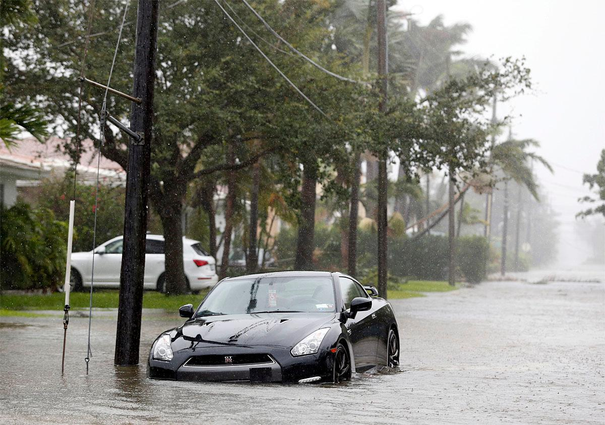 A car is parked on a flooded road as Hurricane Irma passes, Sunday, Sept. 10, 2017, in Surfside, Fla. (AP Photo/Wilfredo Lee)