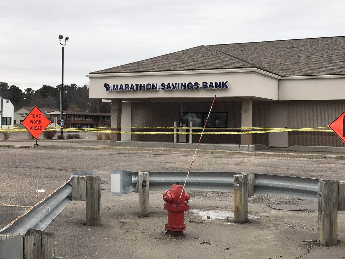 Police tape surrounds the Marathon Savings Bank in Rothschild March 23, 2017, one day after a series of shootings in the area. (WLUK/Gabrielle Mays)