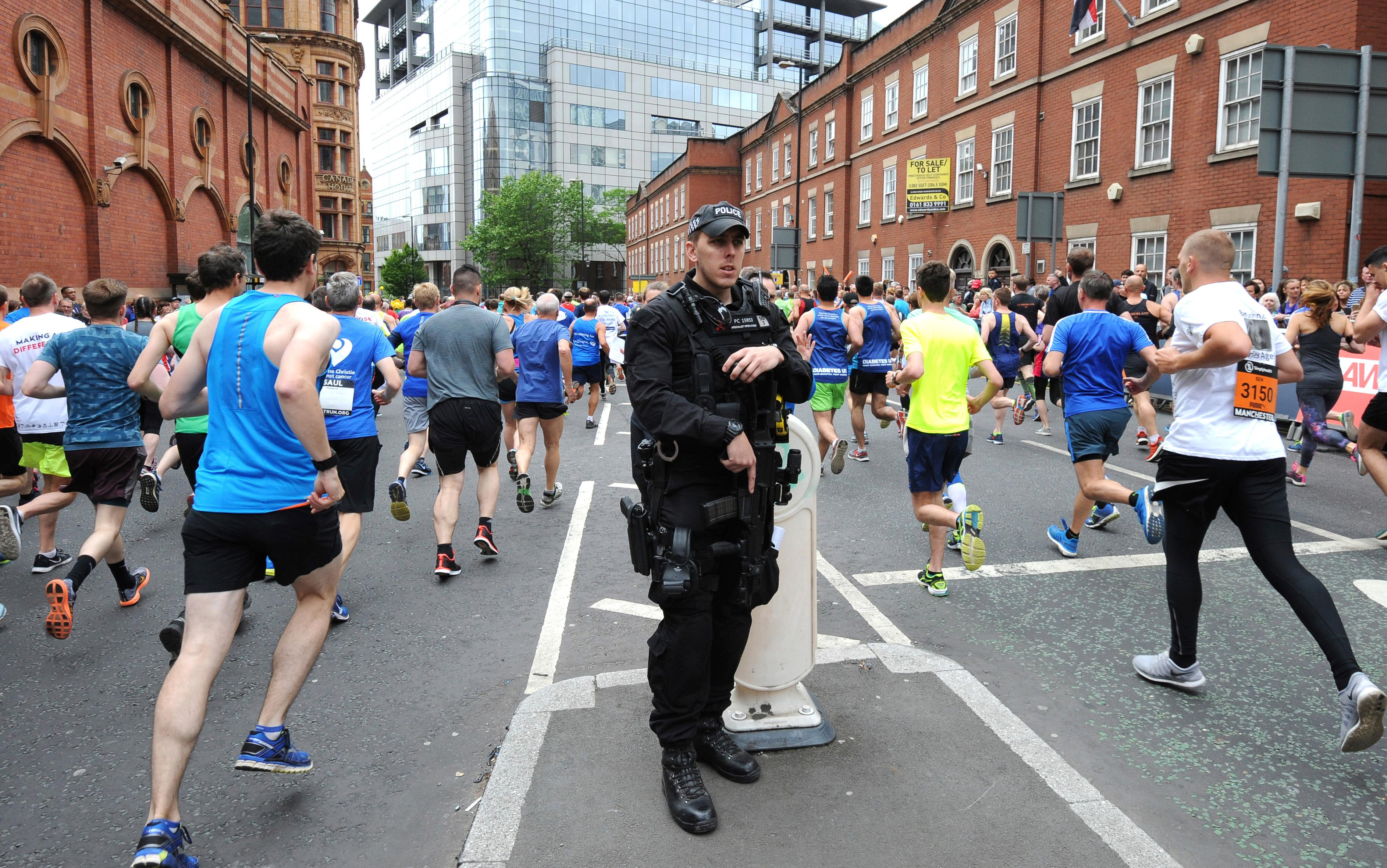 Armed response police stand at the start of the Great Manchester Run in central Manchester, England Sunday May 28 2017. More than 20 people were killed in an explosion following a Ariana Grande concert at the Manchester Arena late Monday evening. (AP Photo/Rui Vieira)