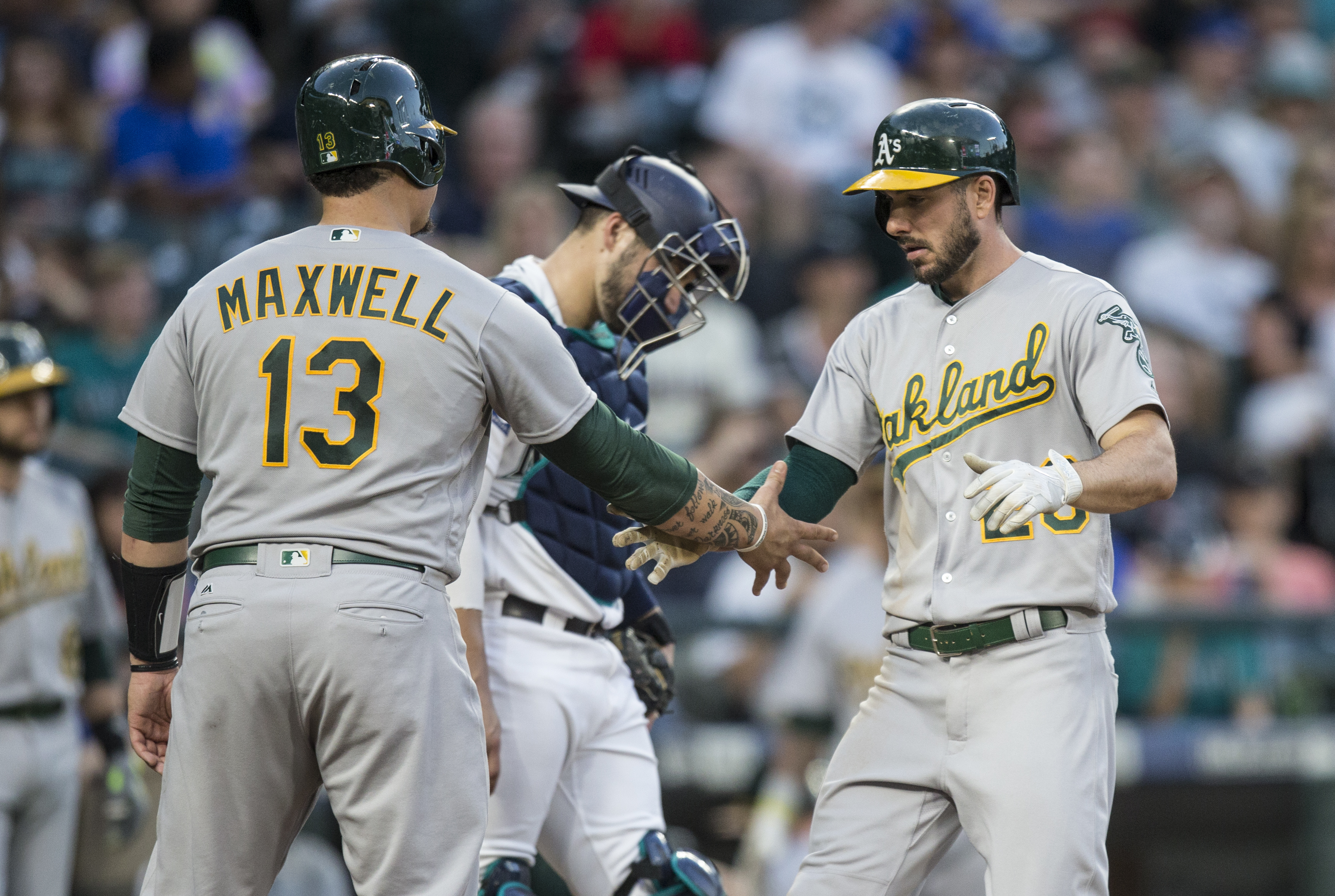 Oakland Athletics' Matt Joyce is congratulated by Bruce Maxwell after hitting a three-run home run off Seattle Mariners relief pitcher Casey Lawrence during the fourth inning of a baseball game on Saturday, Sept. 2, 2017, in Seattle. (AP Photo/Stephen Brashear)