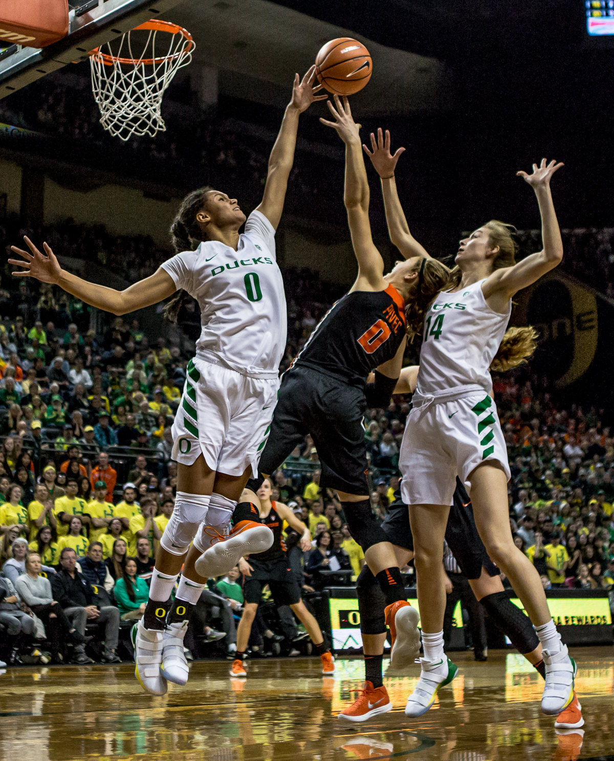 Oregon forward Satou Sabally (#0) blocks an attempted shot by Oregon State guard Mikayla Pivec (#0). The Oregon Ducks defeated the Oregon State Beavers 75-63 on Sunday afternoon in front of a crowd of 7,249 at Matthew Knight Arena. The Ducks and Beavers split the two game Civil War with the Beavers defeating the Ducks on Friday night in Corvallis. The Ducks had four players in double digits: Satou Sabally with 21 points, Maite Cazorla with 16, Sabrina Ionescu with 15, and Mallory McGwire with 14. The Ducks shot 48.4% from the floor compared to the Beavers 37.3%. The Ducks are now 7-1 in conference play. Photo by Ben Lonergan, Oregon News Lab