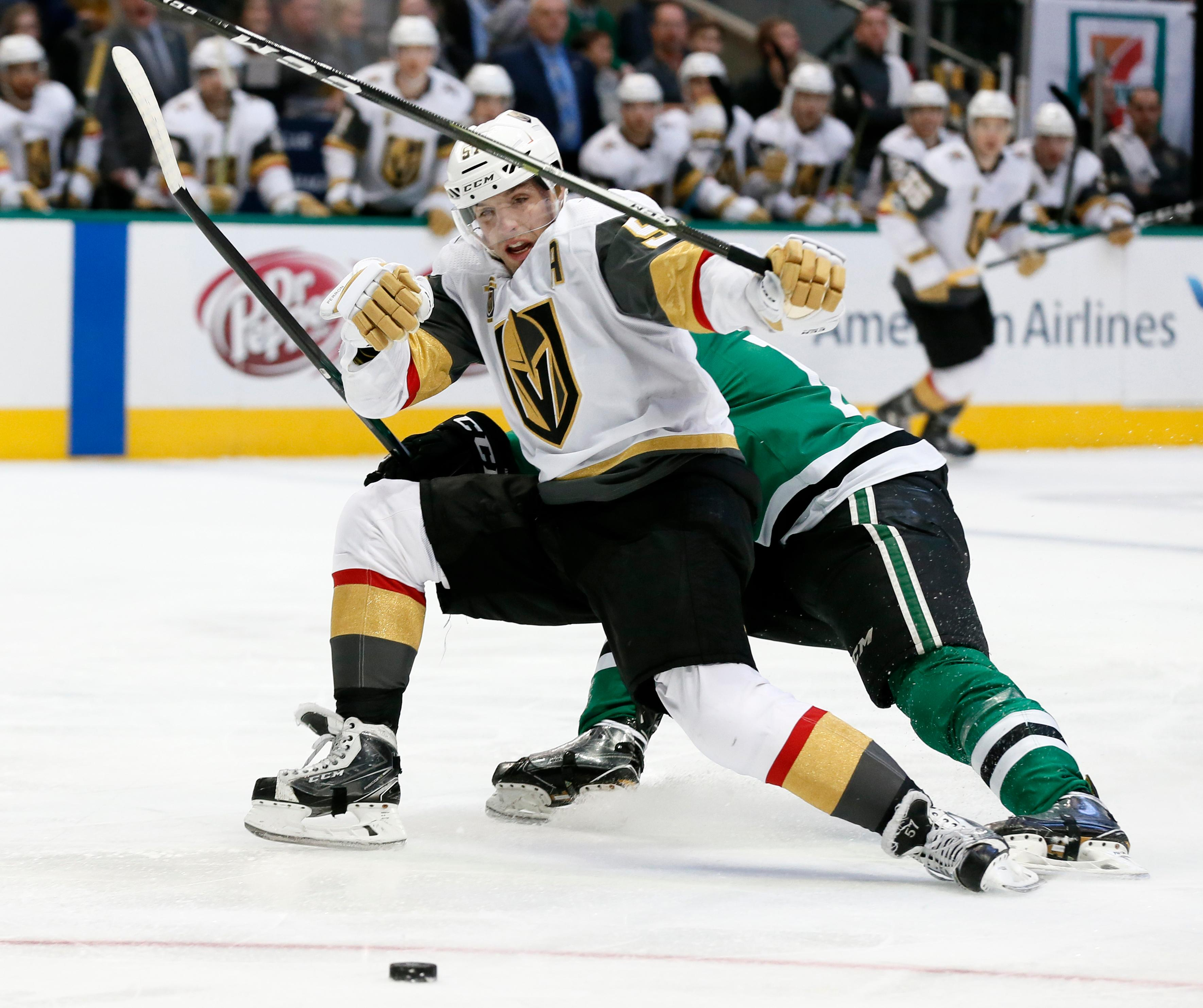 Vegas Golden Knights left wing David Perron (57) loses control of the puck after being hit by Dallas Stars' Radek Faksa during the first period of an NHL hockey game, Saturday, Dec. 9, 2017, in Dallas. (AP Photo/Tony Gutierrez)