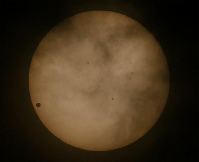 Venus passes in front of the sun, as visible from Hong Kong, Wednesday, June 6, 2012. From the U.S. to South Korea, people around the world turned their attention to the daytime sky on Tuesday and early Wednesday in Asia to make sure they caught the once-in-a-lifetime sight of the transit of Venus.(AP Photo/Vincent Yu)