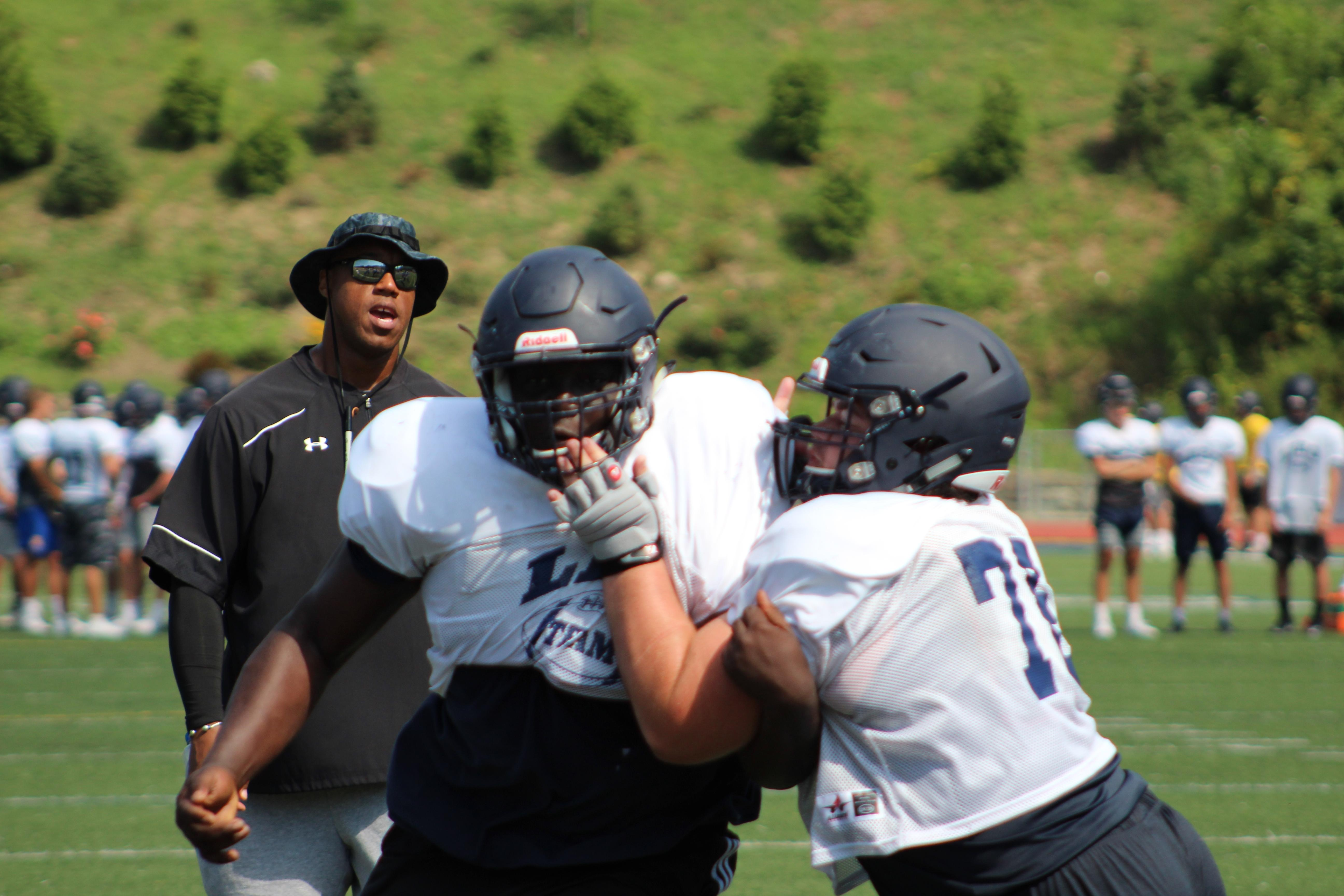 "With former Clarion University and NFL lineman Reggie Wells looking on, Mount Lebanon's J.B. Nelson fights through a block. Wells serves as an assistant coach on the Mount Lebanon staff. Watch the AHN Friday Night Rivals powered by IGS Energy ""Kickoff Special"" Aug. 23 at 7 p.m. on 22 the Point."