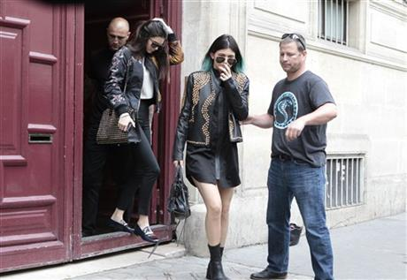 Kendall Jenner, center, and Kylie Jenner, leave Kanye West's Paris apartment, Tuesday, May 20, 2014.