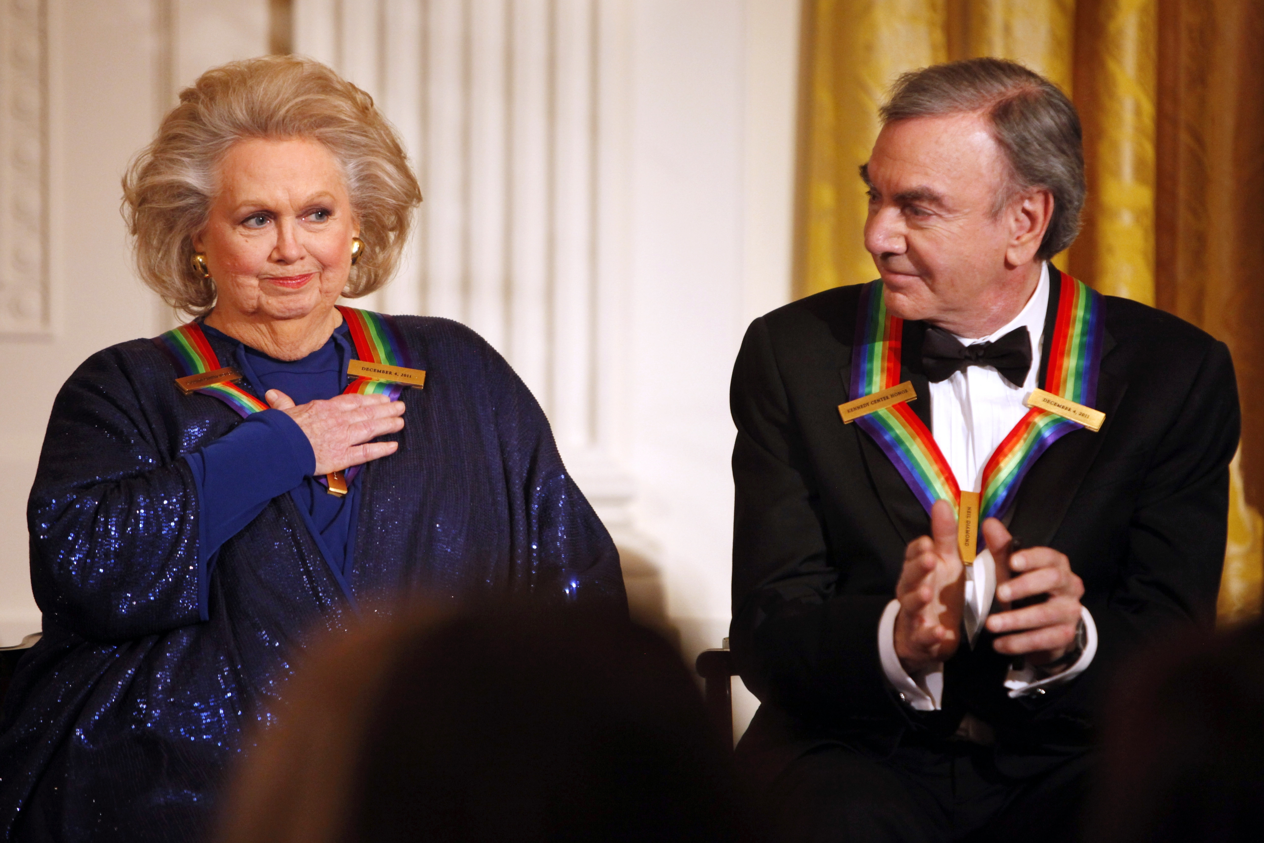FILE - In this Dec. 4, 2011 file photo, actress-singer Barbara Cook, left, reacts to remarks from President Barack Obama, next to fellow 2011 Kennedy Center Honors recipient singer and songwriter Neil Diamond, during at a reception for the honorees in the East Room of the White House, in Washington. Cook, whose shimmering soprano made her one of Broadway's leading ingenues and later a major cabaret and concert interpreter of popular American song, has died. She was 89. (AP Photo/Jacquelyn Martin, File)