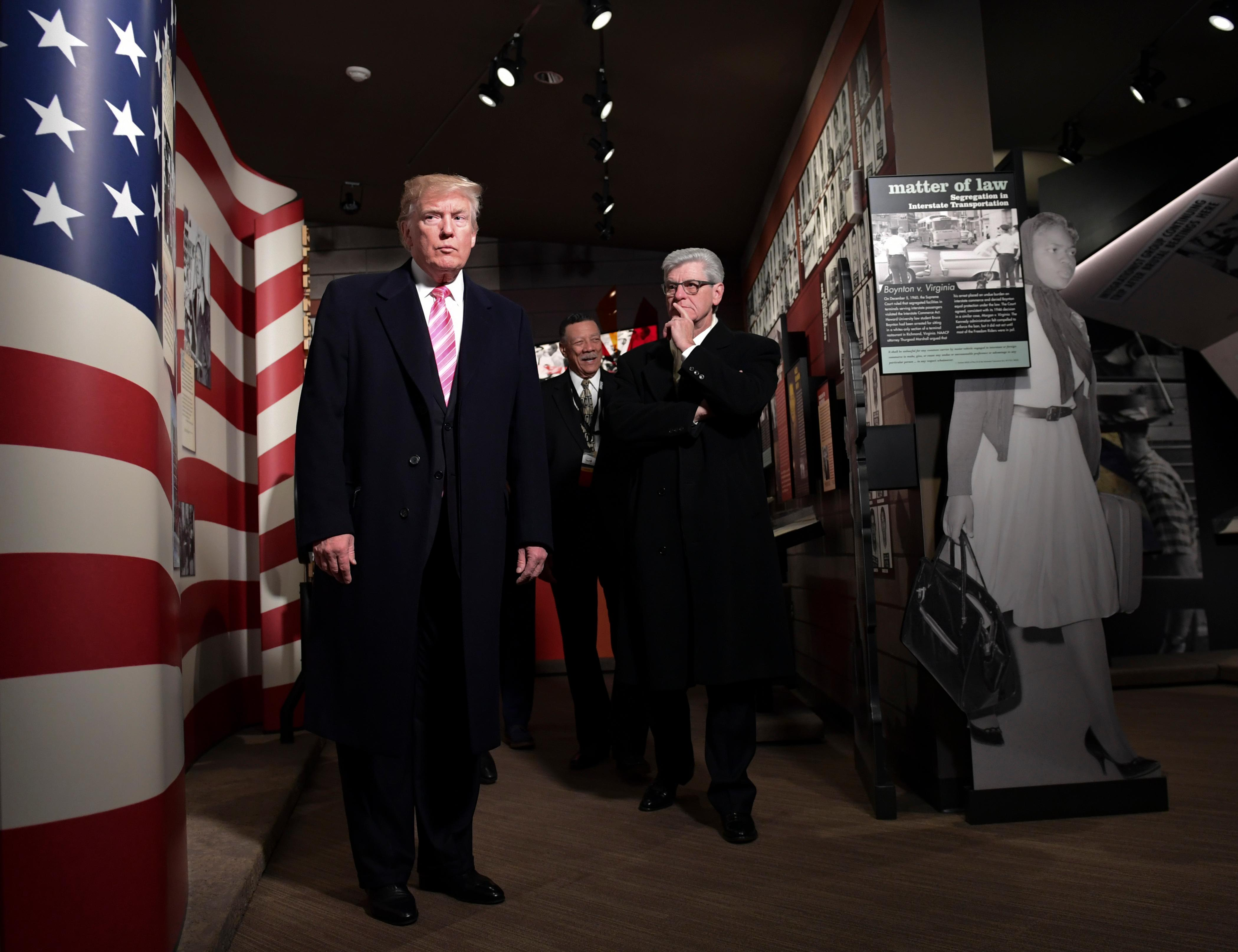President Donald Trump, left, gets a tour of the newly-opened Mississippi Civil Rights Museum in Jackson, Miss., Saturday, Dec. 9, 2017. Mississippi Gov. Phil Bryant, watches at right. (AP Photo/Susan Walsh)