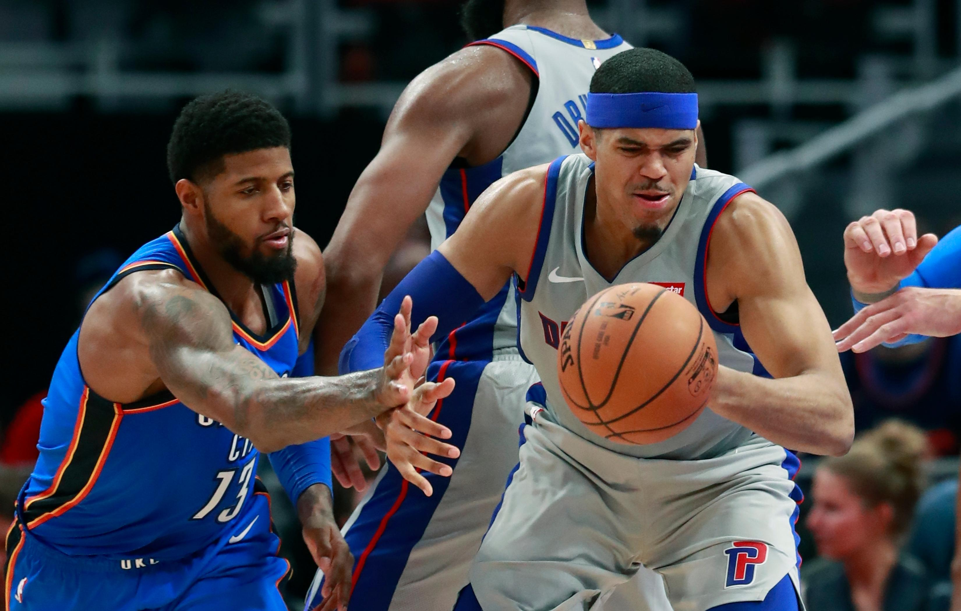 Oklahoma City Thunder forward Paul George (13) knocks the ball away from Detroit Pistons forward Tobias Harris during the second half of an NBA basketball game Saturday, Jan. 27, 2018, in Detroit. (AP Photo/Carlos Osorio)