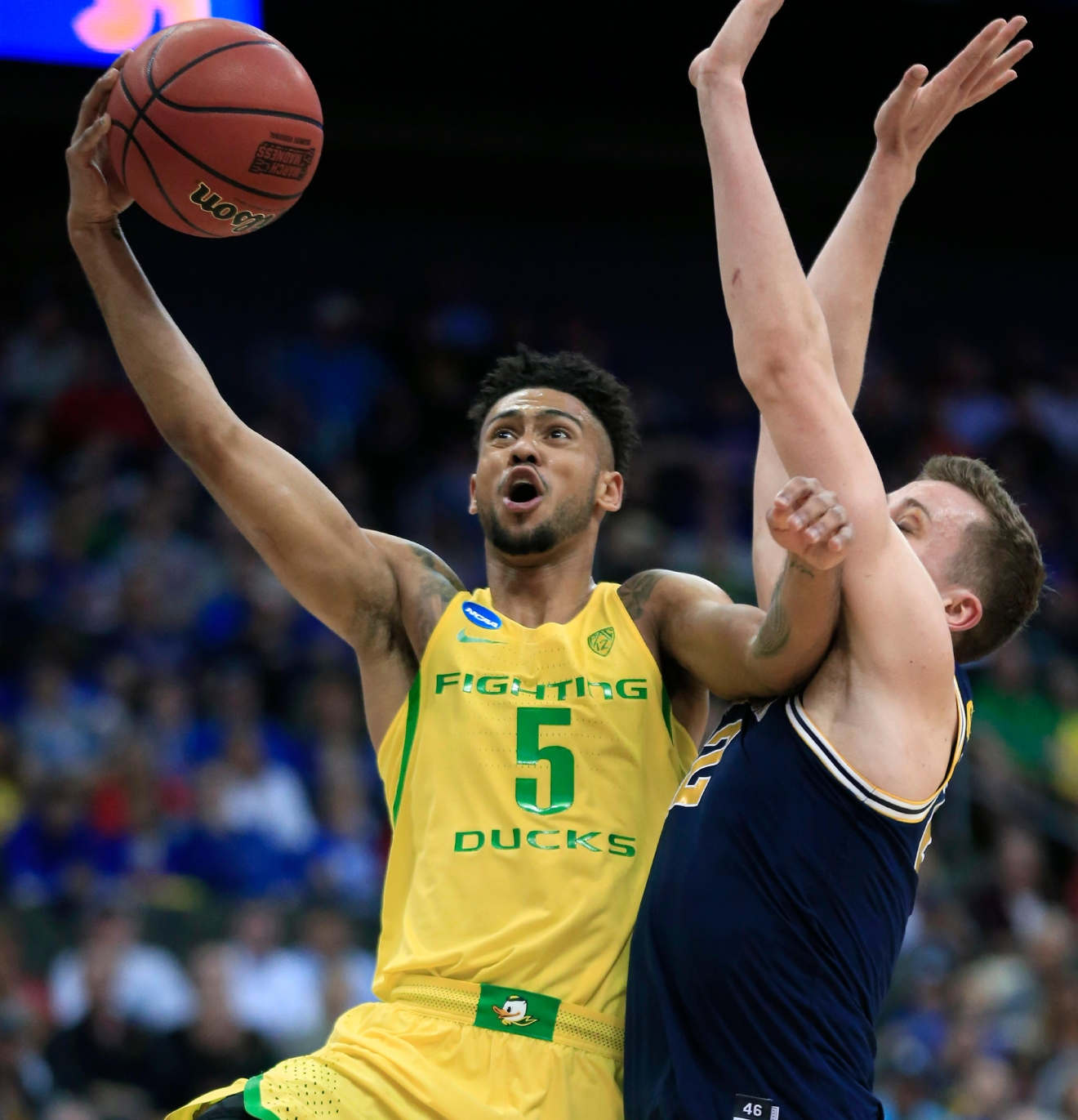 Oregon guard Tyler Dorsey (5) drives to the basket past Michigan guard Duncan Robinson during the first half of a regional semifinal of the NCAA men's college basketball tournament, Thursday, March 23, 2017, in Kansas City, Mo. (AP Photo/Orlin Wagner)