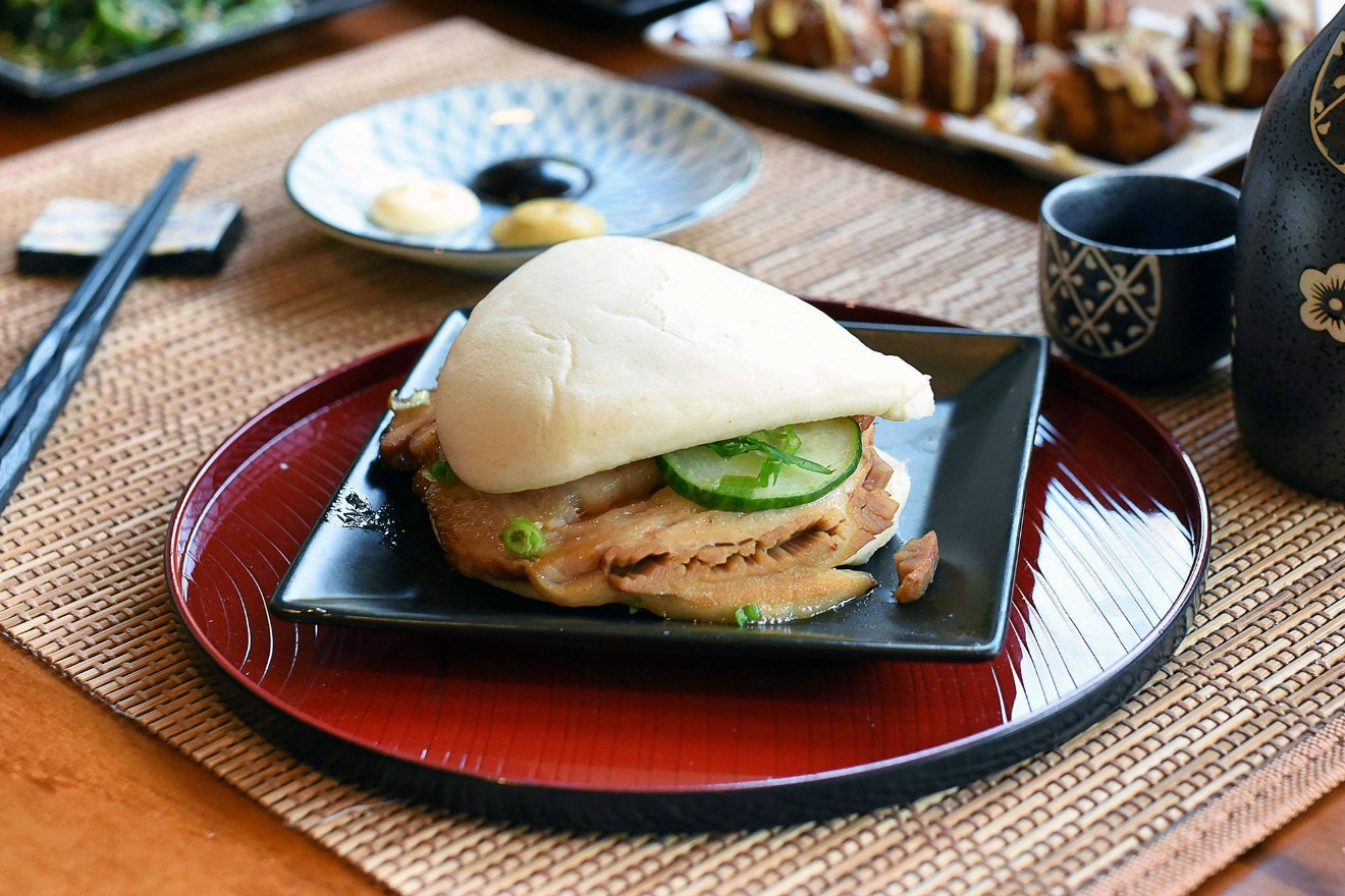 A Japanese Pork Bun, a tender pork belly sandwich made with a fluffy steamed bun with green onions and cucumber. (Image Courtesy: Kizuki Ramen & Izakaya Facebook Page)