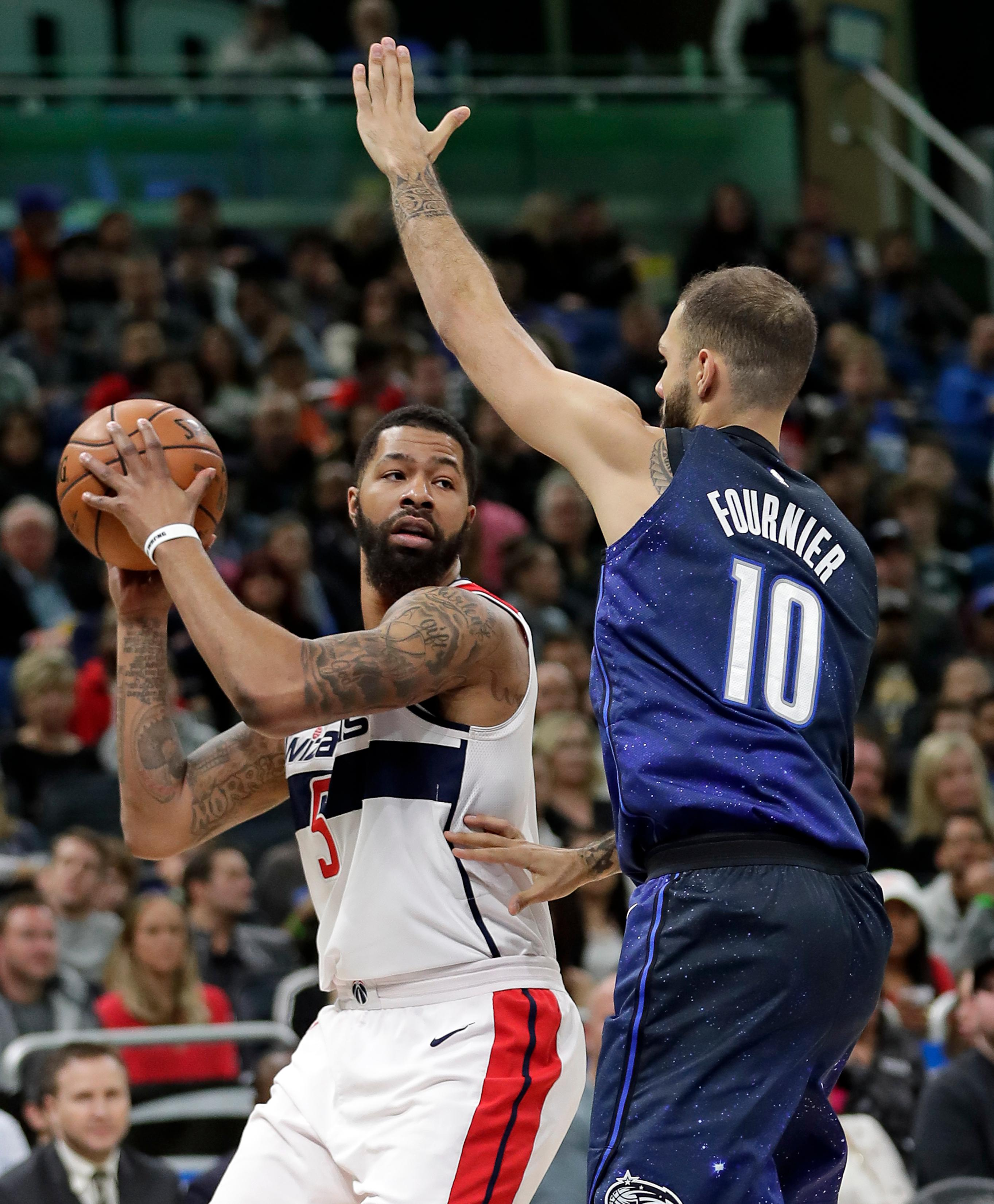 Washington Wizards' Markieff Morris, left, looks to pass the ball around Orlando Magic's Evan Fournier (10) during the first half of an NBA basketball game Saturday, Feb. 3, 2018, in Orlando, Fla. (AP Photo/John Raoux)