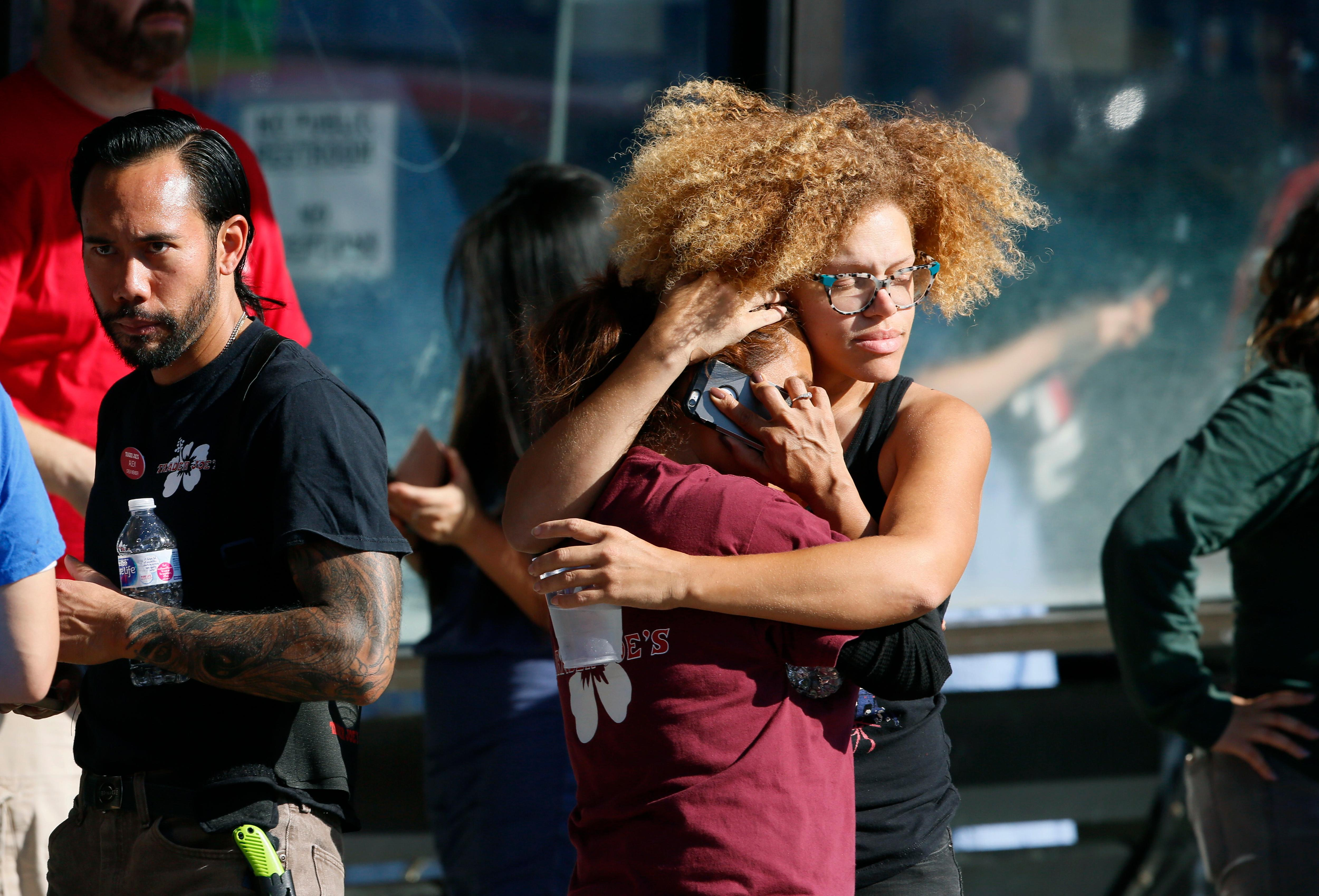 Unidentified Trader Joe's supermarket employees hug after being evacuated by Los Angeles Police after a gunman barricaded himself inside  the store in Los Angeles Saturday, July 21, 2018. Police believe a man involved in a standoff at the Los Angeles supermarket shot his grandmother and girlfriend and then fired at officers during a pursuit before he crashed into a utility pole outside the supermarket and ran inside the store. Hours after he took hostages in the store, the suspect surrendered. (AP Photo/Damian Dovarganes)