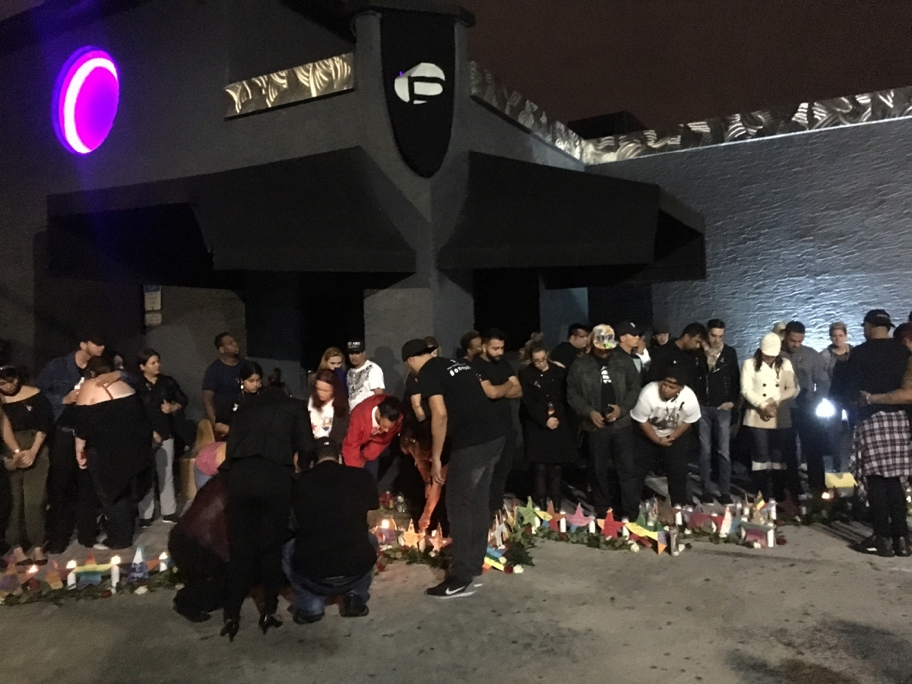 Family and friends of victims, and survivors of the Pulse nightclub attack gather at the club at 2:02 a.m., the time when the shooting started, on Monday, Dec. 12, 2016, the six-month anniversary of the tragedy. (Christal Hayes/Orlando Sentinel via AP)