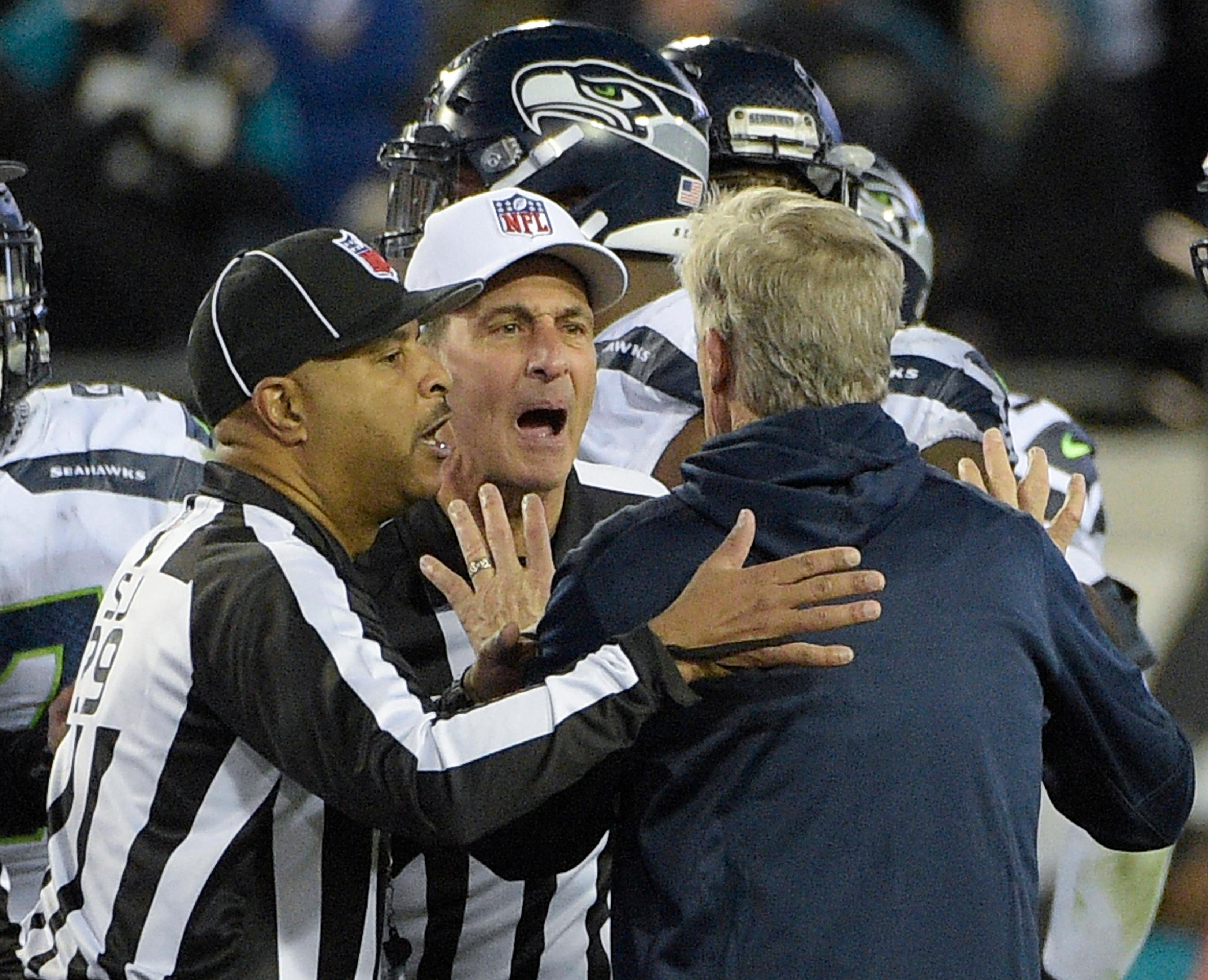 Seattle Seahawks head coach Pete Carroll is held back by officials after he ran on the field during the final moments of an NFL football game Sunday, Dec. 10, 2017, in Jacksonville, Fla. Jacksonville won 30-24. Carroll got flagged for coming onto the field. (AP Photo/Phelan M. Ebenhack)