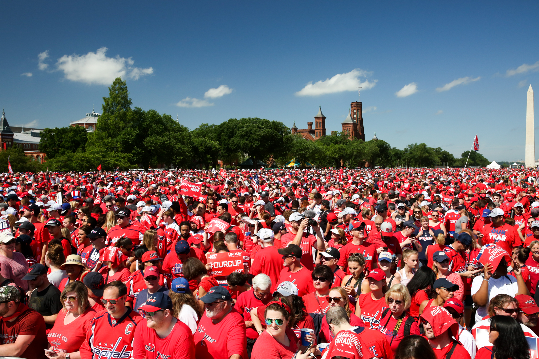 The National Mall was a sea of red as the Washington Capitals paraded the Stanley Cup through the streets of D.C. Although the cup barely left Alex Ovechkin's brawny-but-tender embrace, the players reveled in the fervor, shotgunning beers as they rode on top of buses along Constitution Avenue before rallying on The Mall.(Amanda Andrade-Rhoades/DC Refined)
