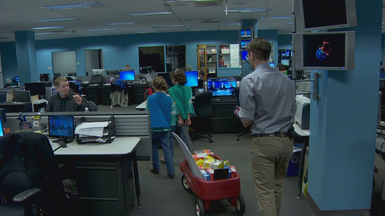 Ian Parker (right) takes Sidra and her sister through the newsroom to gather donations.