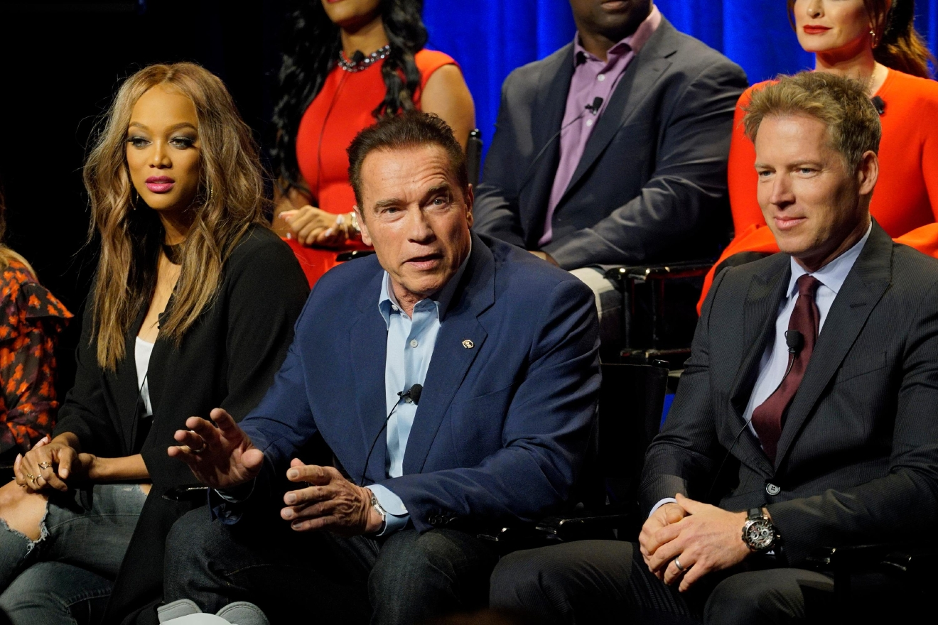 "In this Friday, Dec. 9, 2016 photo provided by NBC, Tyra Banks, from left, Arnold Schwarzenegger, Patrick Knapp Schwarzenegger attend a press junket for ""The New Celebrity Apprentice,"" in Los Angeles. Schwarzenegger, star of the new version of the television show, is unfazed that President-elect Donald Trump has retained a producer's stake in the show. Schwarzenegger said Friday that it's just business, comparable to his situation when he became California's governor and retained a screen credit and kept earning royalties for the ""Terminator"" movie. (Paul Drinkwater/NBC via AP)"