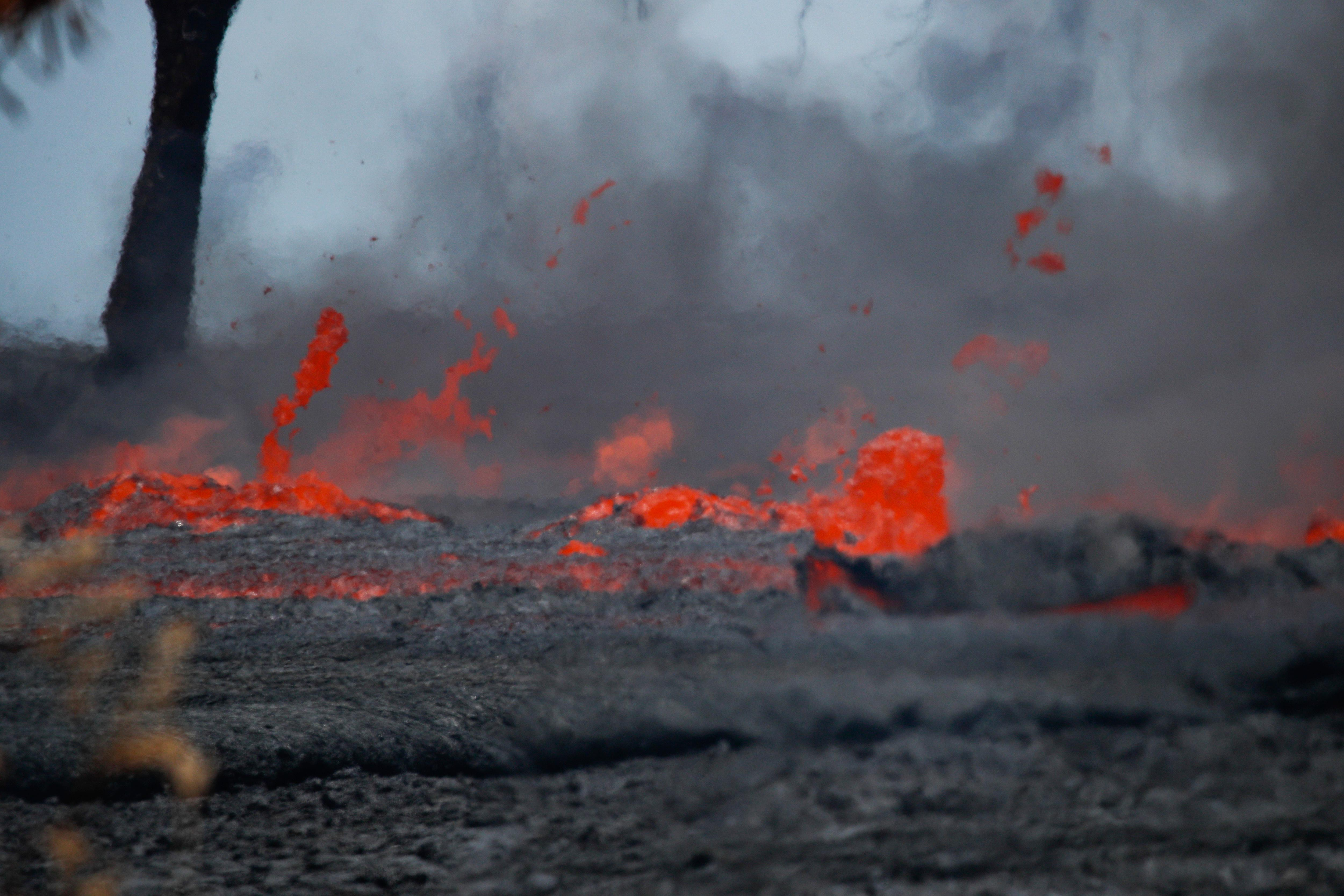 Fissures spew lava in the Leilani Estates subdivision near Pahoa, Hawaii, Tuesday, May 22, 2018. Authorities were racing Tuesday to close off production wells at a geothermal plant threatened by a lava flow from Kilauea volcano on Hawaii's Big Island. (AP Photo/Jae C. Hong)