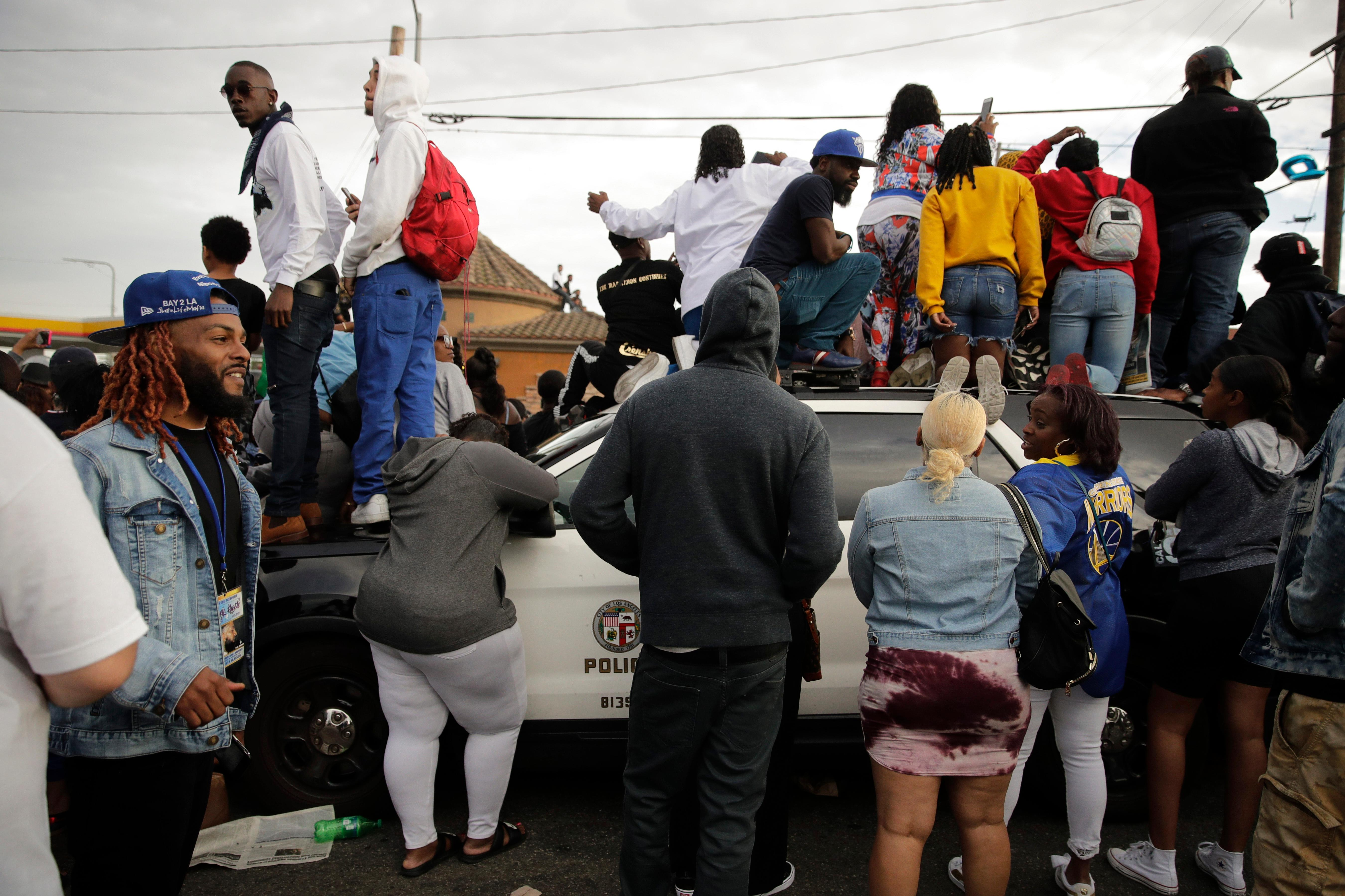 People climb on a police vehicle to watch a hearse carrying the casket of slain rapper Nipsey Hussle Thursday, April 11, 2019, in Los Angeles. (AP Photo/Jae C. Hong)