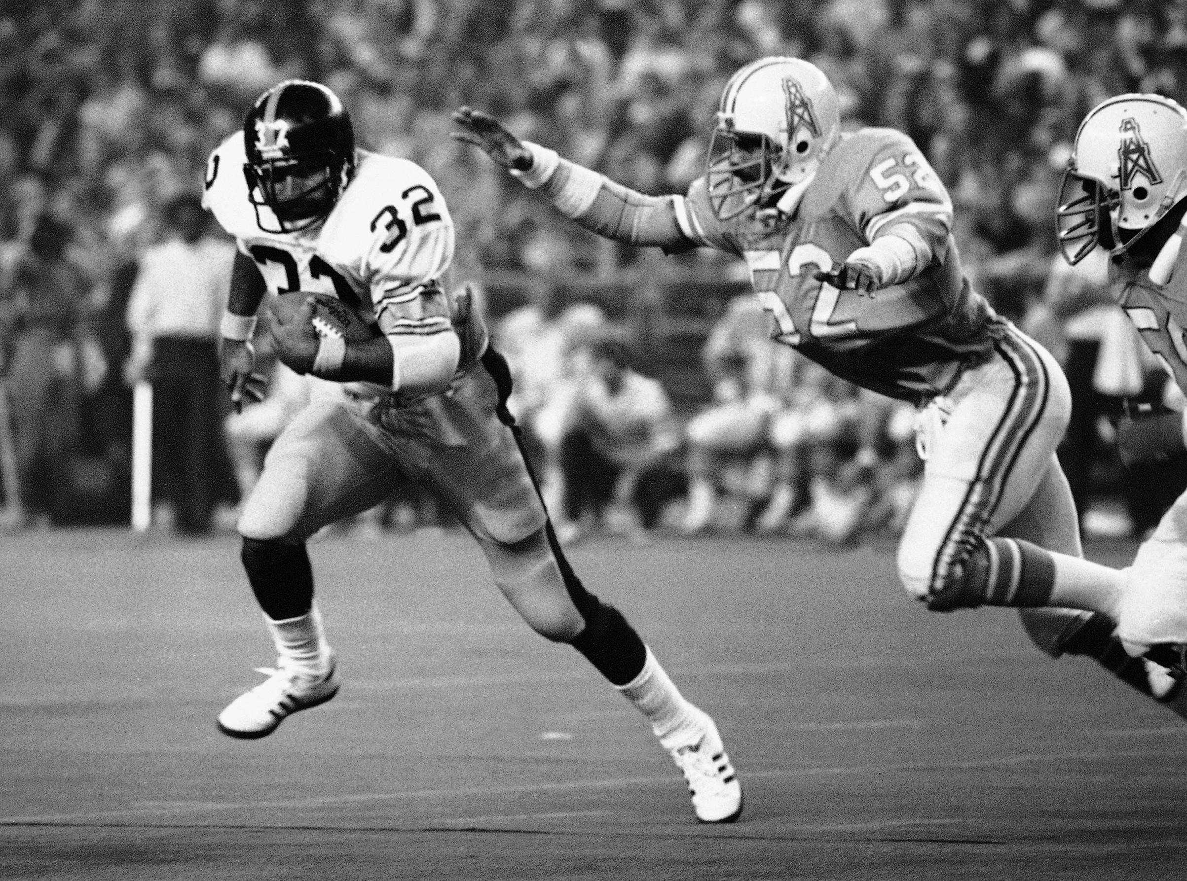 FILE - In this Dec. 3, 1978, file photo, Pittsburgh Steelers running back Franco Harris (32) picks up 10 yards as he turns the corner as Houston Oilers' Robert Brazile (52) makes a dive to latch on to Harris to make the stop, during an NFL football game in Houston. Brazile was elected to the Pro Football Hall of Fame on Saturday, Feb. 3, 2018. (AP Photo/Ed Kolenovsky, File)