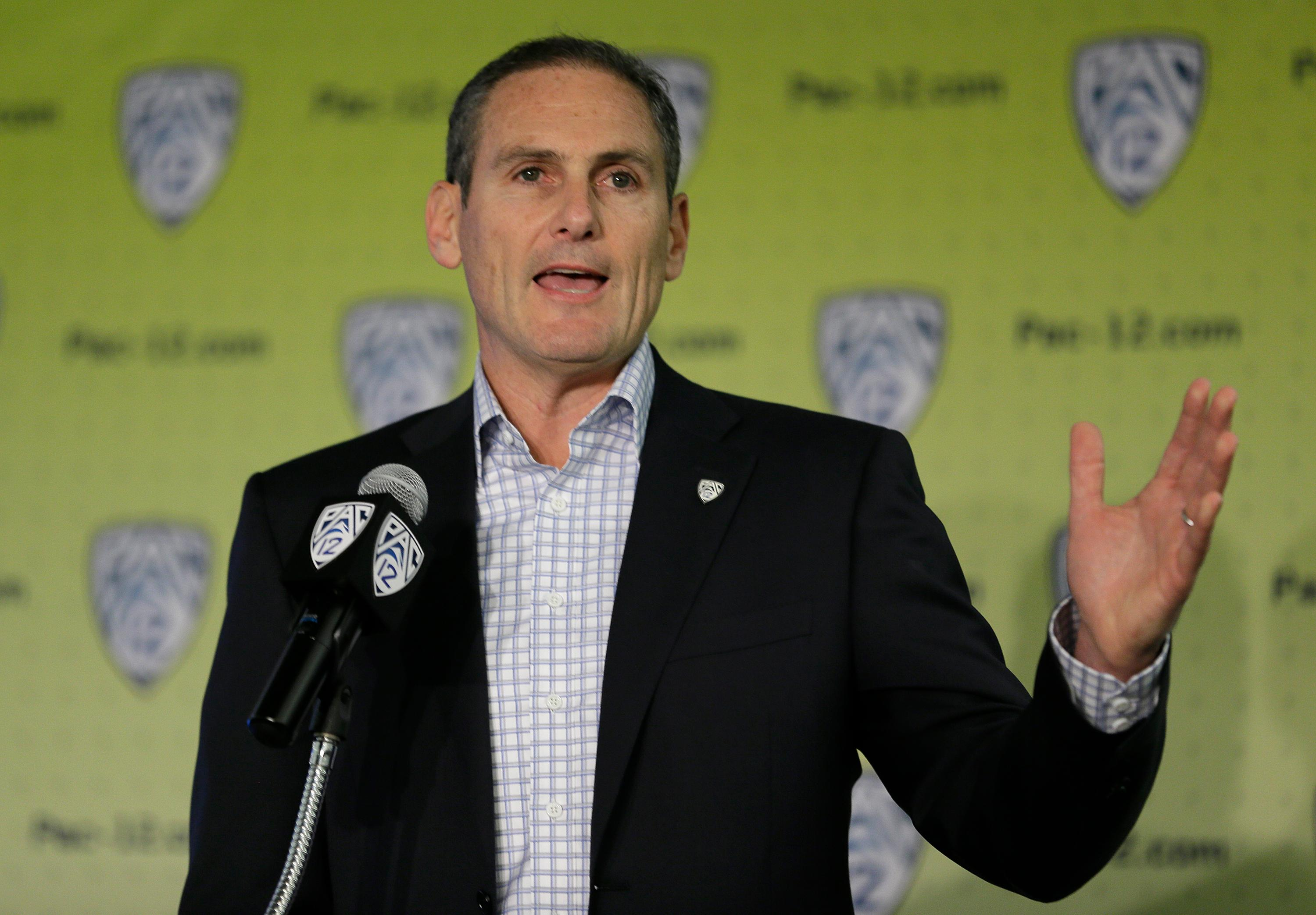 FILE - In this Oct. 12, 2017, file photo, Pac-12 commissioner Larry Scott gestures while speaking a NCAA college basketball Pac-12 media day, in San Francisco. A Pac-12 task force on reforming college basketball is recommending an end to the NBA's one-and-done rule, allowing players to return to school even after they are drafted, and that the NCAA facilitate access to agents for high school players. The Pac-12 announced the recommendations from its task force on Tuesday, March 13, 2018, and its report has been sent to the NCAA's commission on college basketball, headed by former Secretary of State and Stanford University Provost Condoleezza Rice. (AP Photo/Eric Risberg, File)
