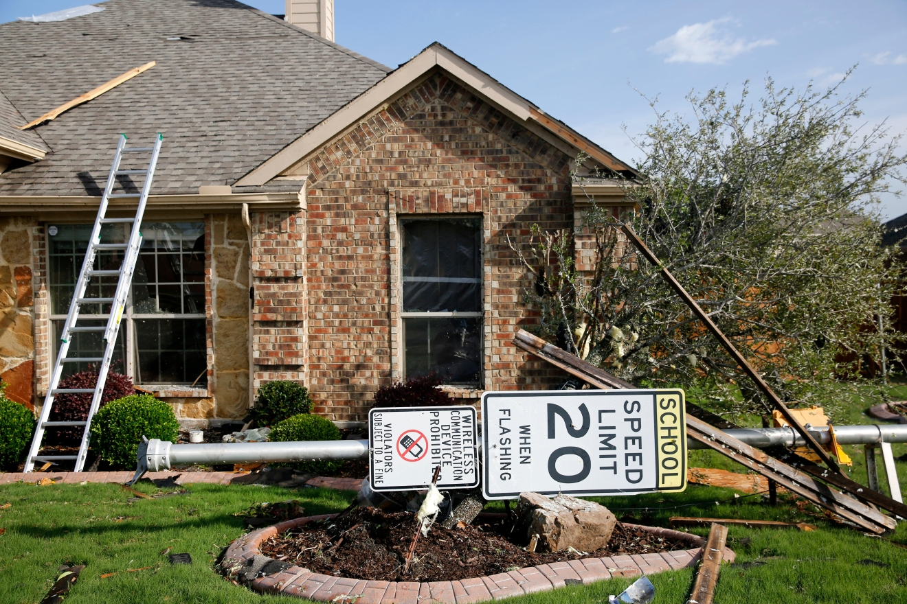 A sign lays in the yard of a damaged home following a storm in the early hours of the morning in Rockwall, Texas on Wednesday, March 29, 2017.  A powerful storm system with winds exceeding 60 mph has damaged homes in suburban Dallas, knocked out power to tens of thousands across Texas and brought heavy rain that inundated some areas. (Rose Baca/The Dallas Morning News via AP)